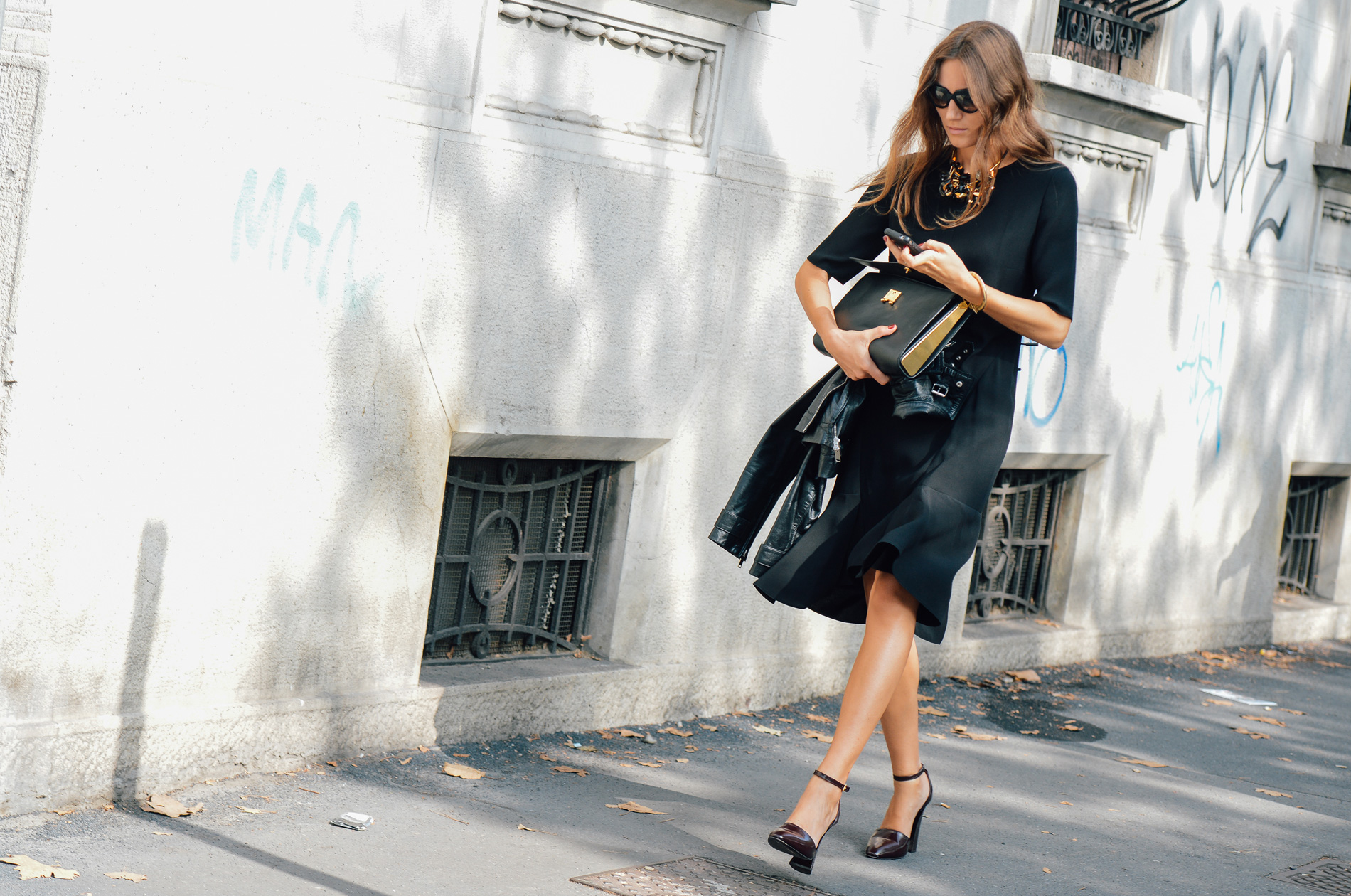 French Chic is all about decoding the Secrets of Paris Fashion, like this Parisian woman who's teamed a well-cut skirt and top with a sleek square handbag and gold statement necklace.