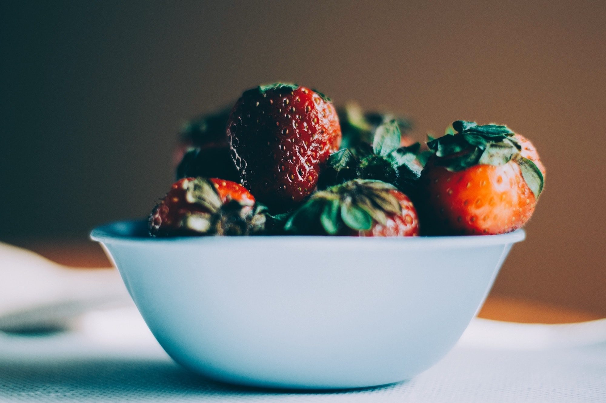 A bowl of ripe hand-picked strawberries on a table.