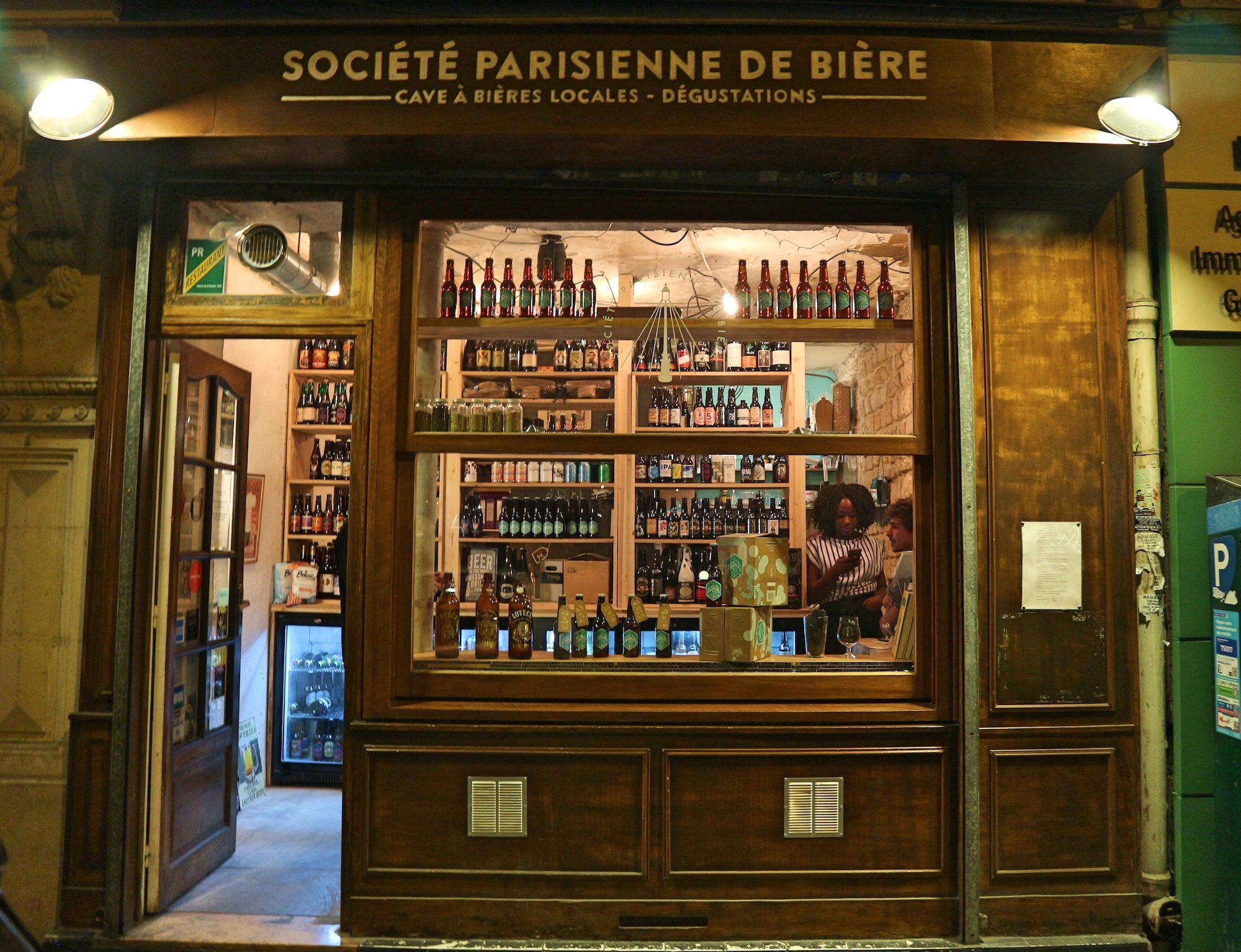 Craft beer shop in Paris, La Société Parisienne de Bière in the Batignolles neighborhood with its artisanal wooden facade.