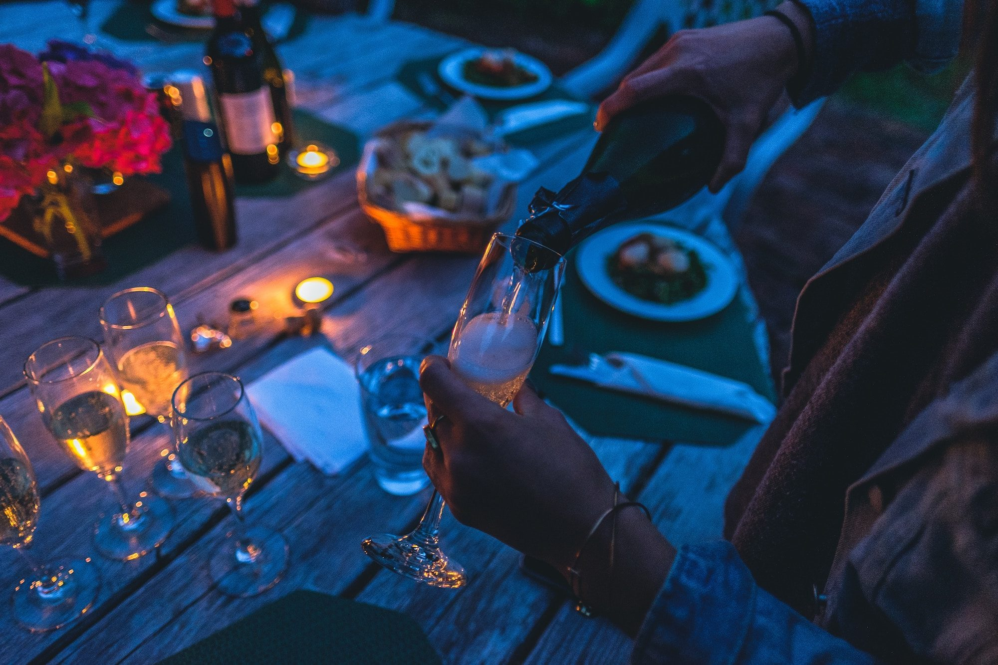 A woman pouring a glass of champagne at an outdoor candle-lit dinner on New Year's Eve.