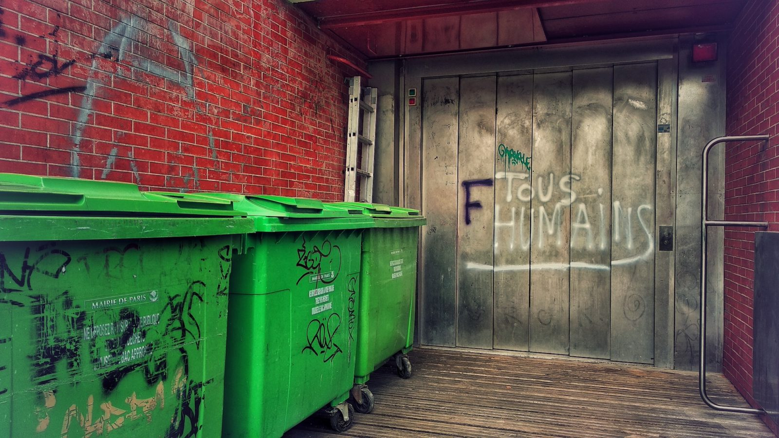 HiP Paris Blog explores France's plastic ban on cups, straws and all single use plastic to reduce waste which applies to everyone, because as the graffiti reads on the wall here next to the large green bins, 'we are all human'.