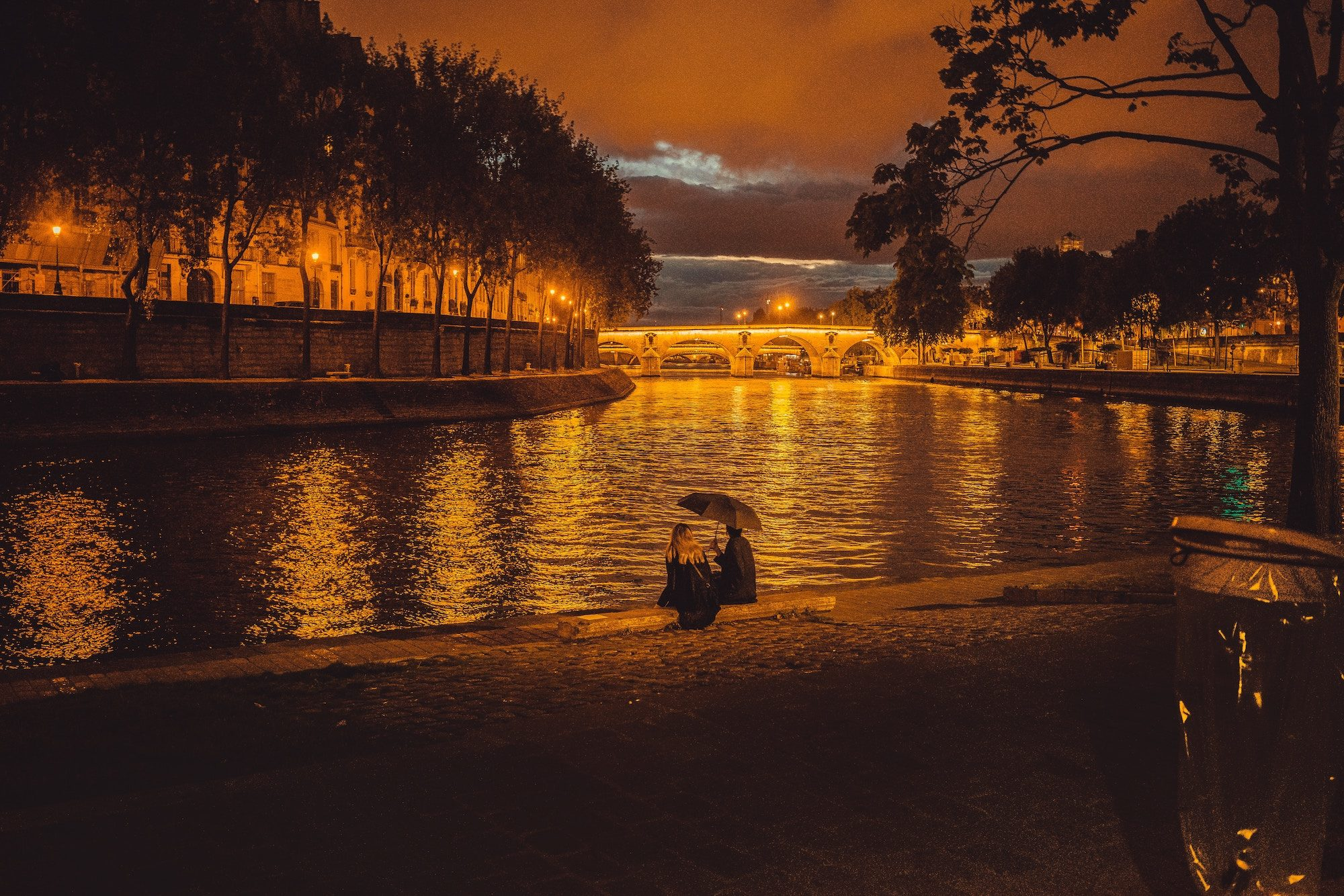 A couple having a date in the rain, sitting on the banks of the River Seine.