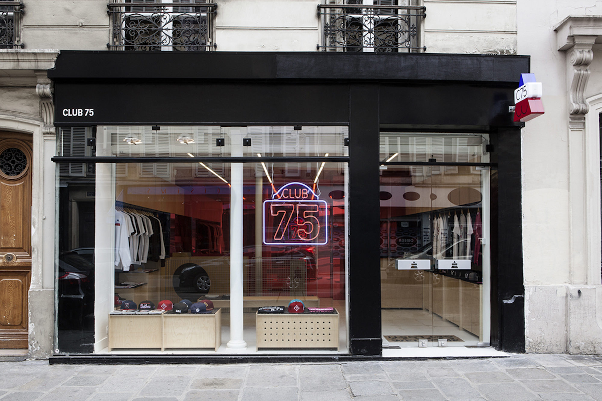 The window of Club 75 with a neon sign of the name of the store in Paris.