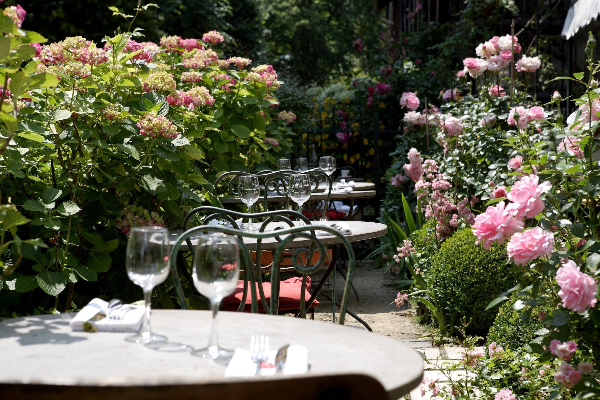 Les Etangs de Corot Hotel garden with tables slotted among the pink rose bushes.