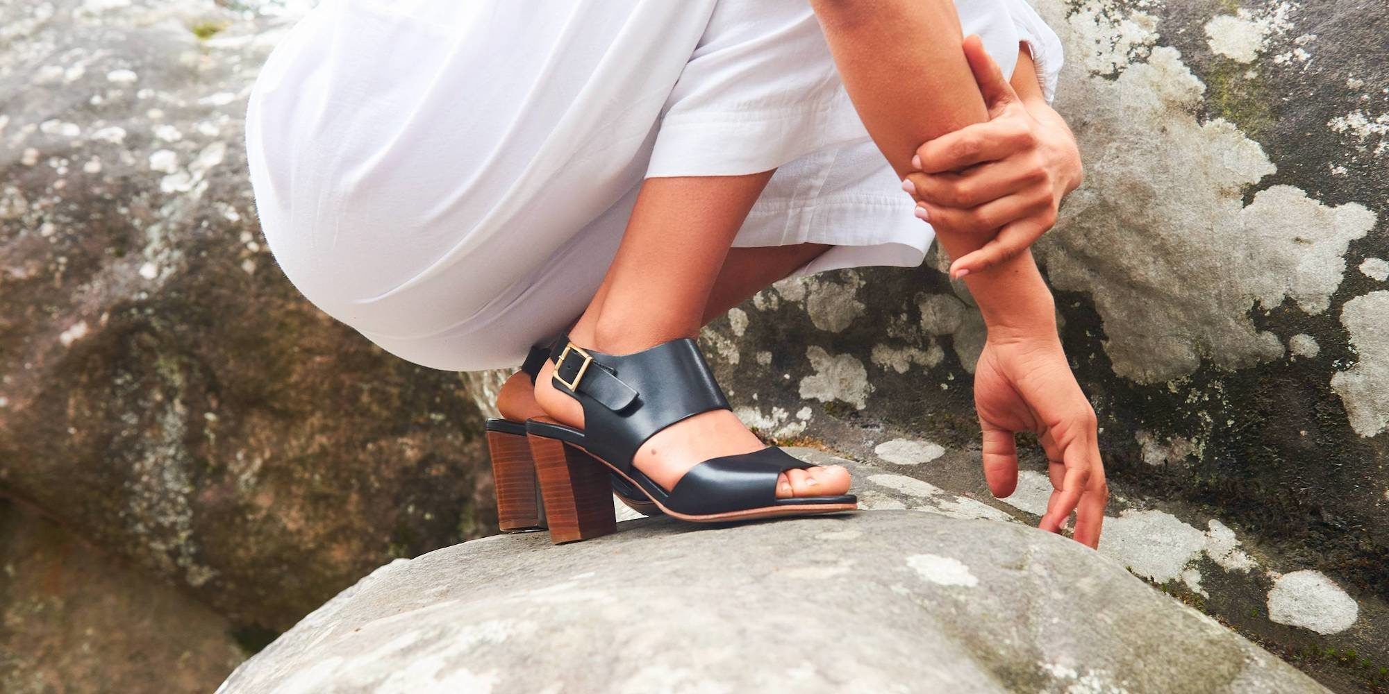 High-heeled black leather sandals by Anthology Paris worn by a girl wearing white trousers and crouching on a rock.