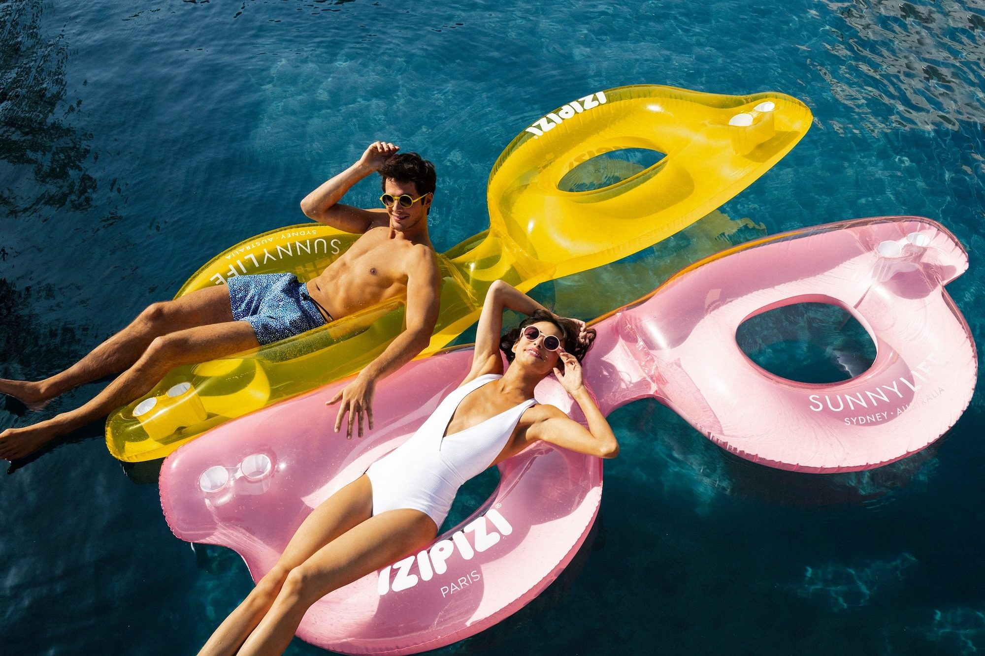 French brand IZIPIZI creates trendy and youthful glasses and sunglasses for women, men, kids and babies like those worn by this man and woman floating on huge floats in the shape of glasses on the sea.