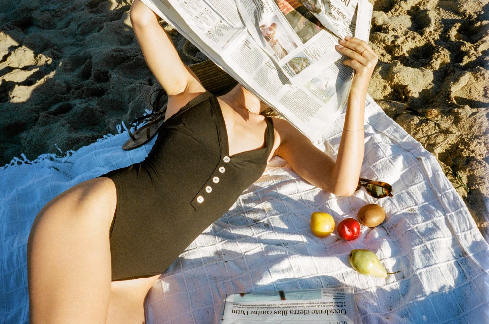 A woman lying on a beach, Italian newspaper open as she reads it and wears a black swimsuit from Jeanne Damas' French brand Rouje.