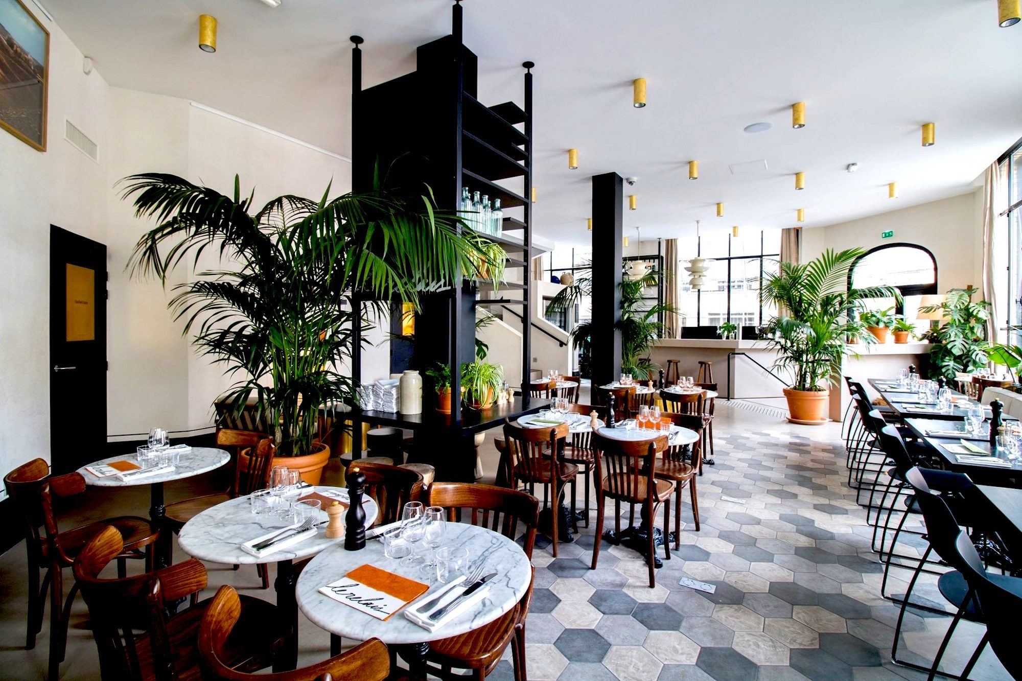 The main dining space at Le Relais restaurant in Paris, a light and bright space with potted plants and tiled floors.