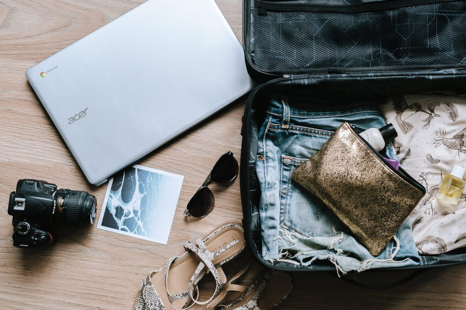 An open suitcase being packed for a summer vacation in Paris with a laptop, camera, sandals, sunglasses and other summer clothes.