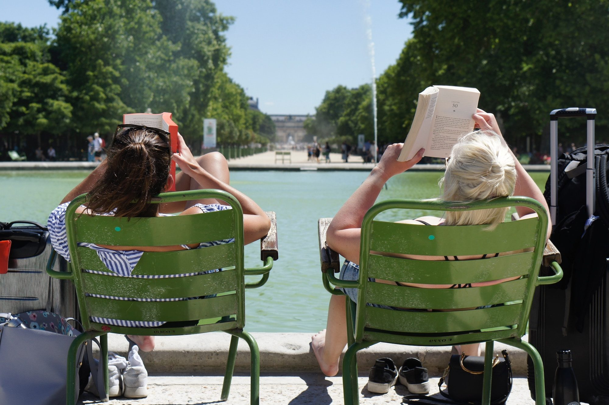 "Two women leaning back in chairs by the water feature at the Jardin des Tuileries in Paris while reading books in the sunshine. They probably said ""bonjour"" even if they don't know one another."