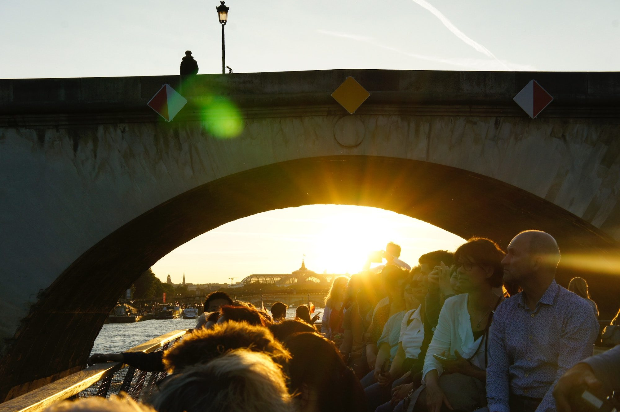Tourists on a barge boat on the River Seine as the sun sets above the Grand Palais as seen peeping out from under one of the bridges straddling the river.