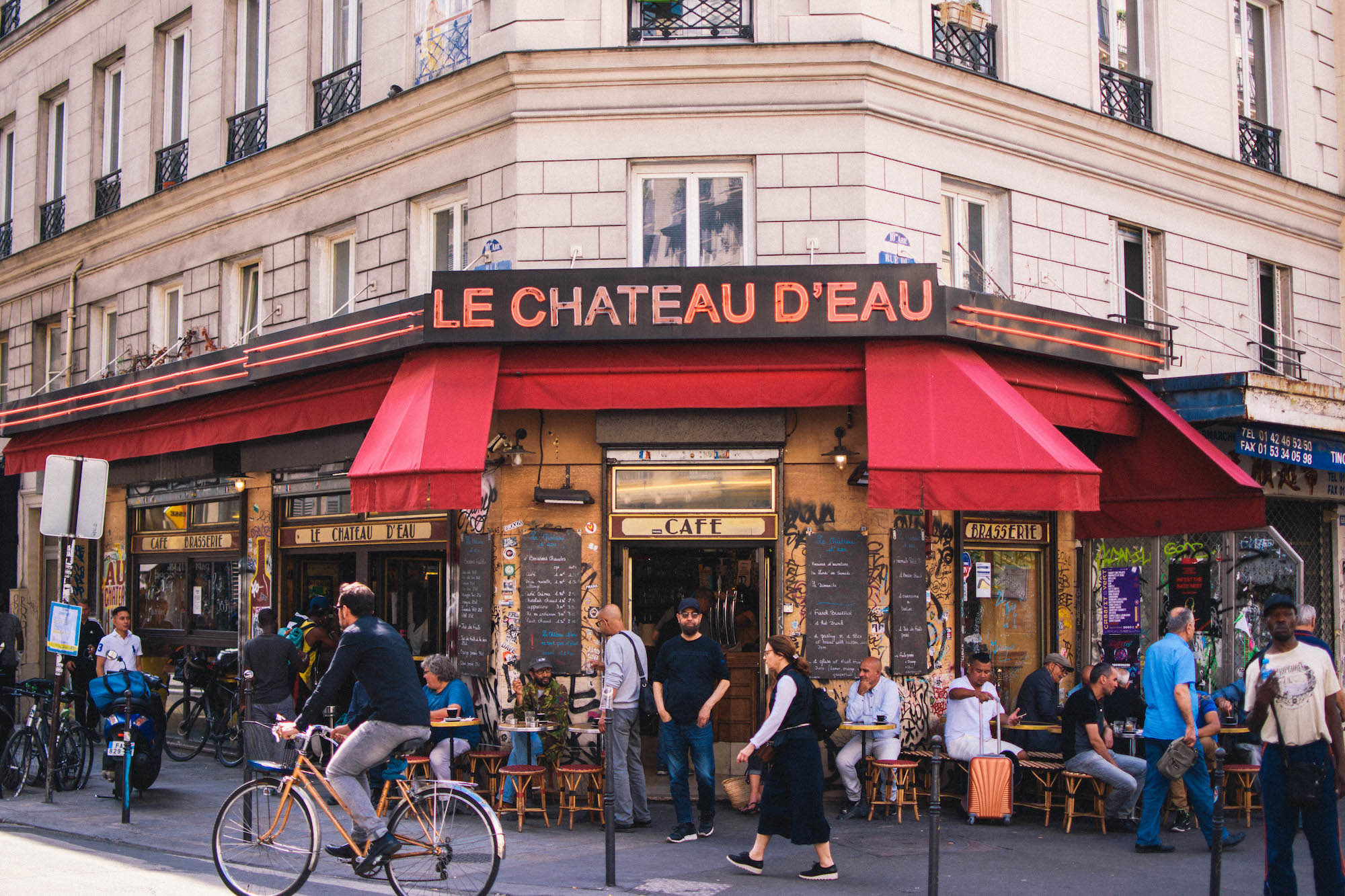 Outside a typical Parisian bistro called 'Le Chateau d'Eau' with a red awning and people sitting at tables outside.