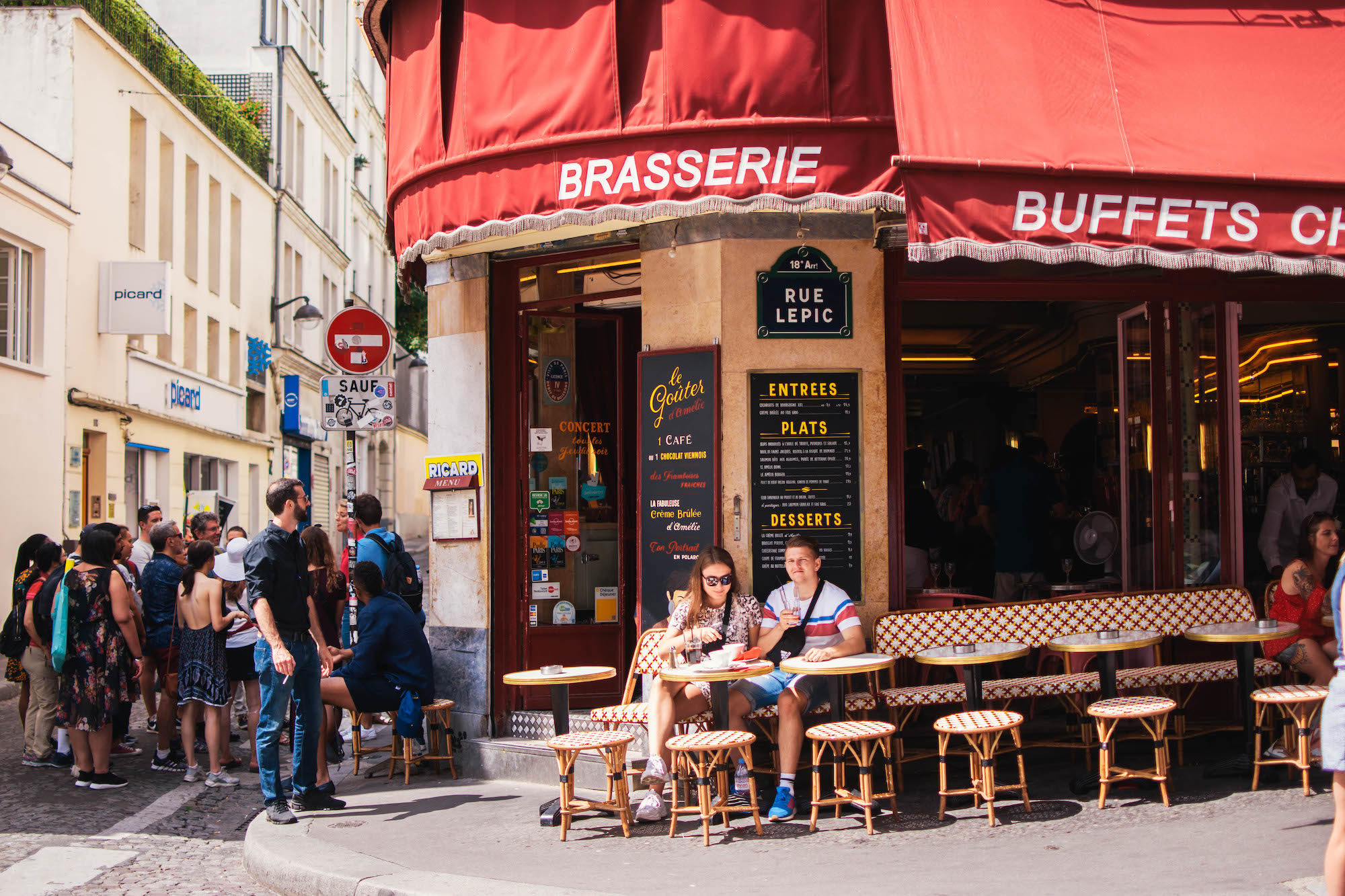 A typical Parisian brasserie with a red awning and people sitting on the terrace in the sunshine.