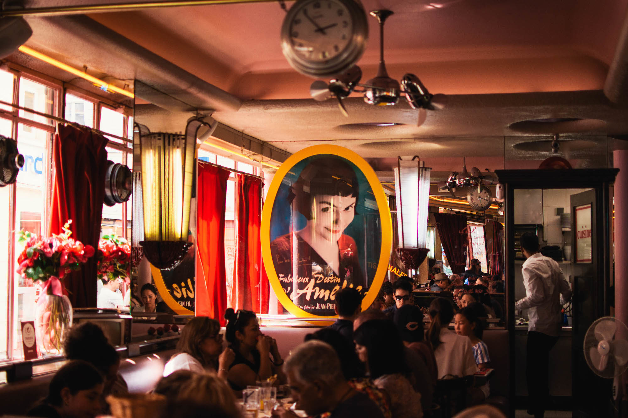 """Inside the Café des 2 Moulins, otherwise known as the café in the movie """"Amélie"""", with an image of Amélie printed on a glass pane and people sat in booths."""