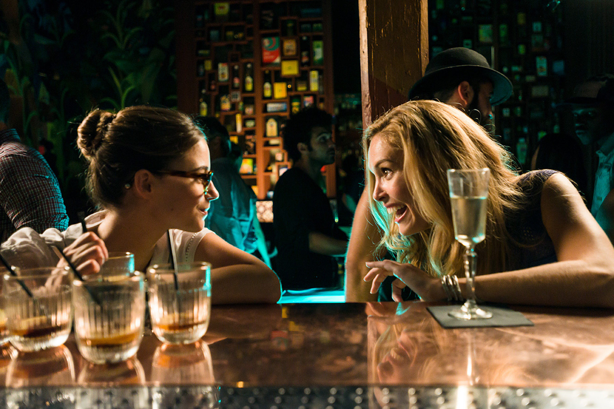 A still from the film 'Blind Date' with two women having drinks at the counter of a bar and chatting.