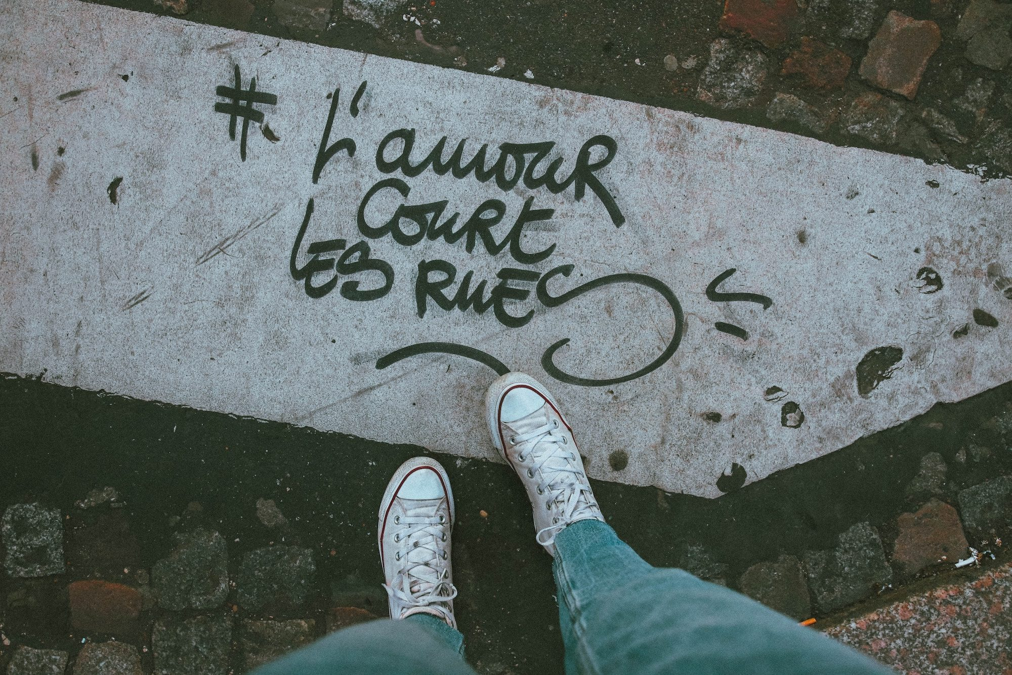 'L'Amour court les rues' (love flows through the streets) inscribed on a zebra crossing, which is a slogan that can now be found all over the city.