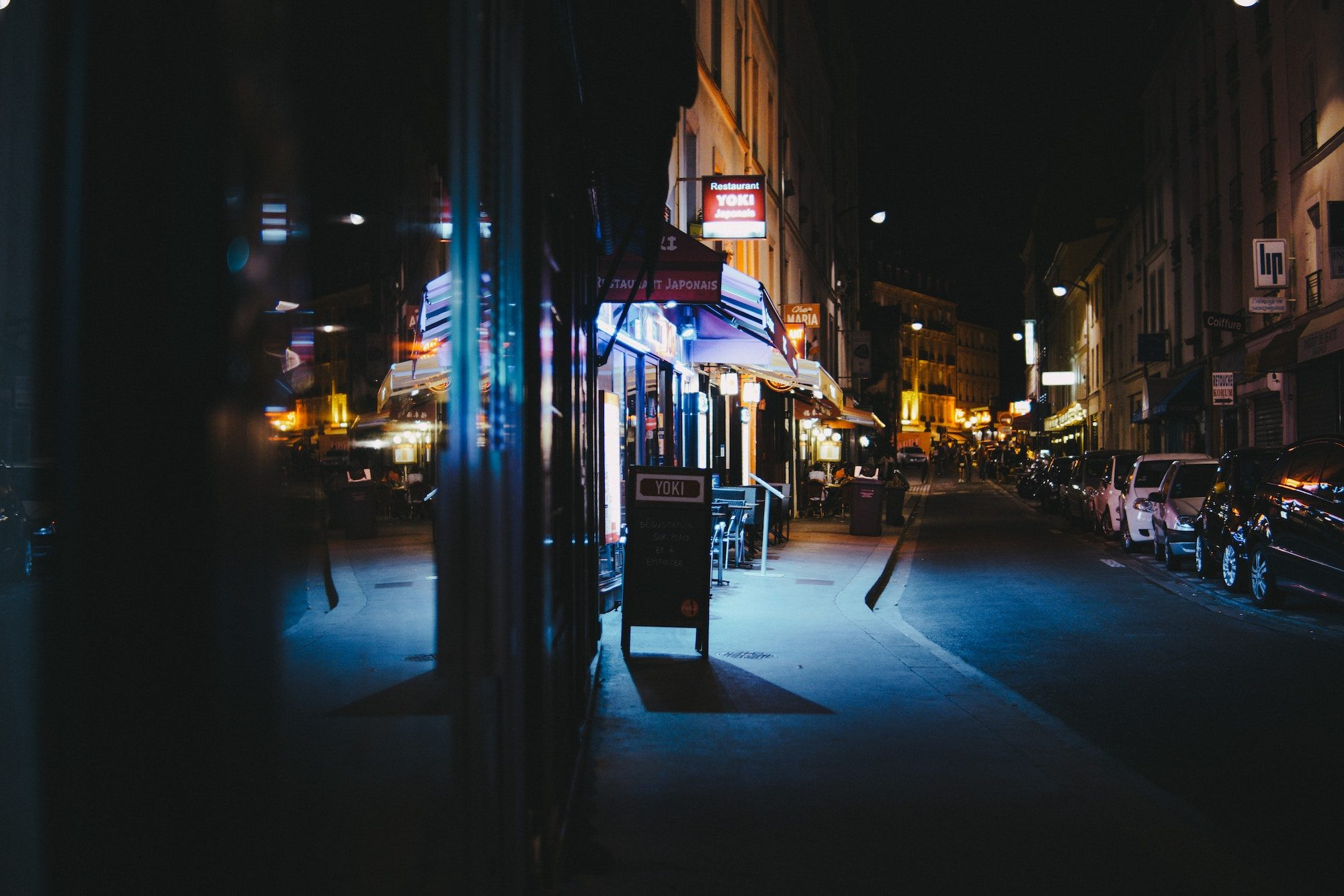 A night street scene in Paris of neon shop signs lining on empty street.