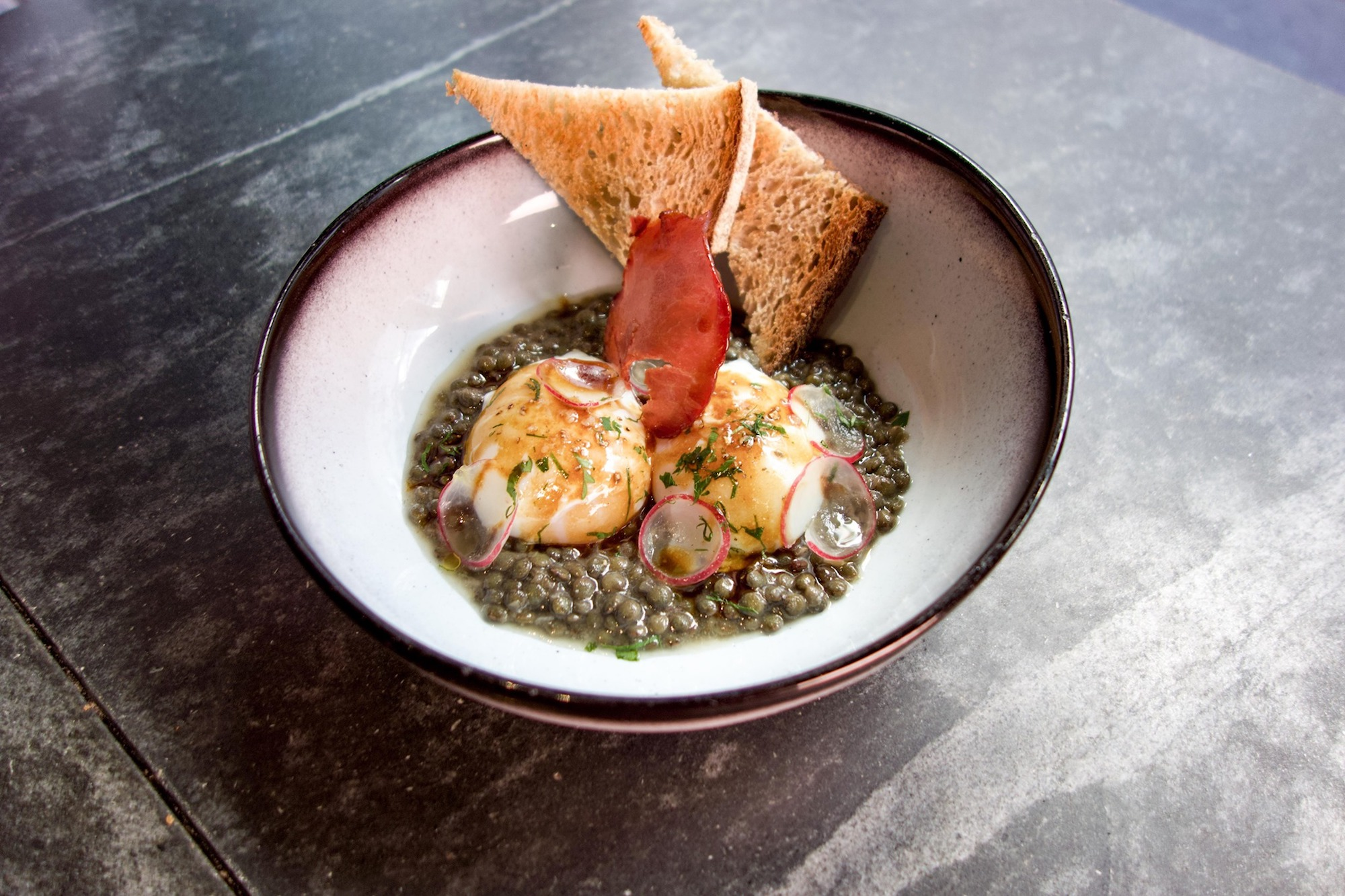 Atelier Maître Albert, a cozy, mode rôtisserie in Paris' 5th arrondissement, offers a simple, yet hearty, dish of lentils, perfectly poached eggs, and toast with ephemeral radish slices.