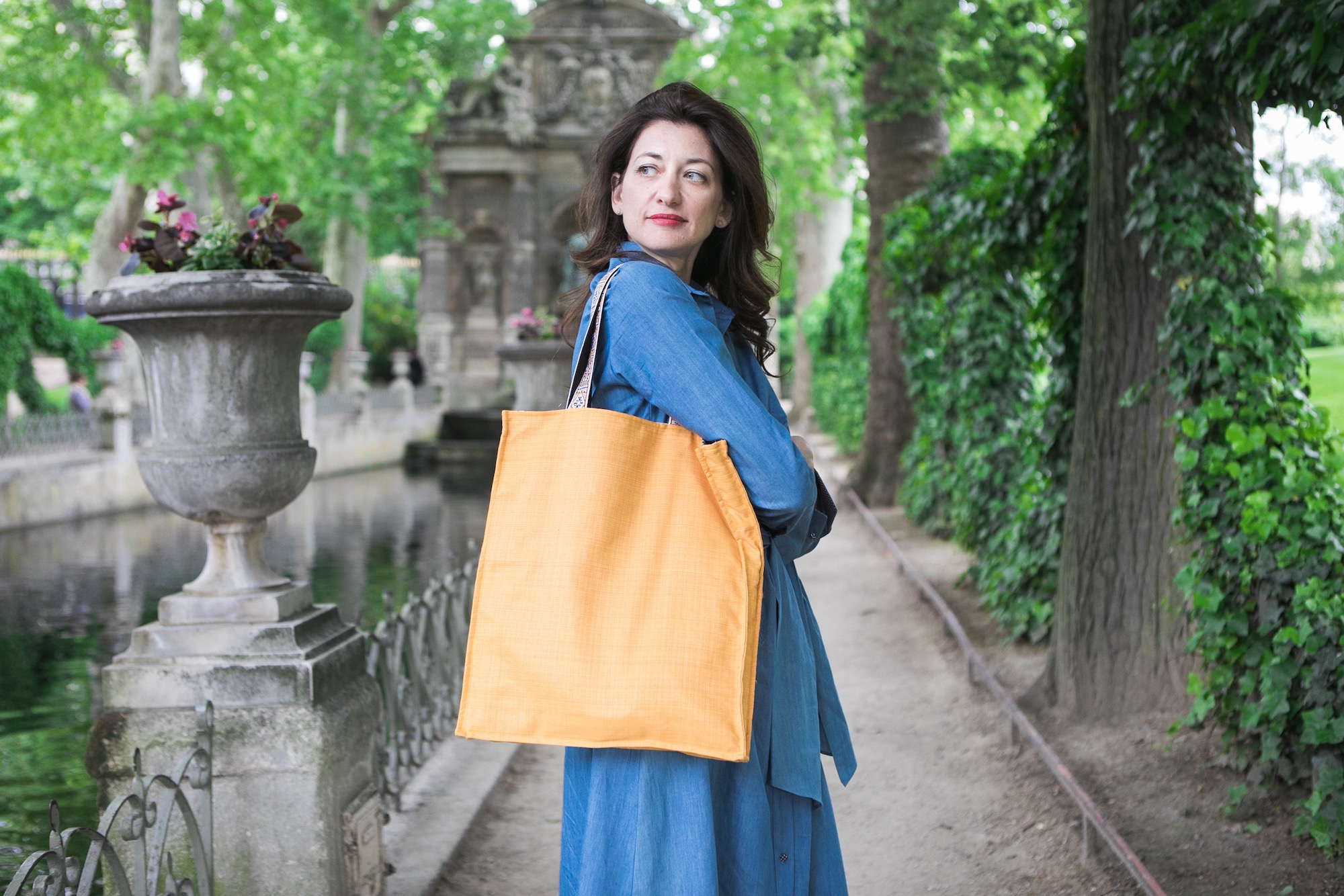 Kasia Dietz, founder of her eponymous handbag line, enjoys a lush spring day at the Medici Fountain in the Jardin du Luxembourg, one of her creamy orange tote bags slung over her shoulder.