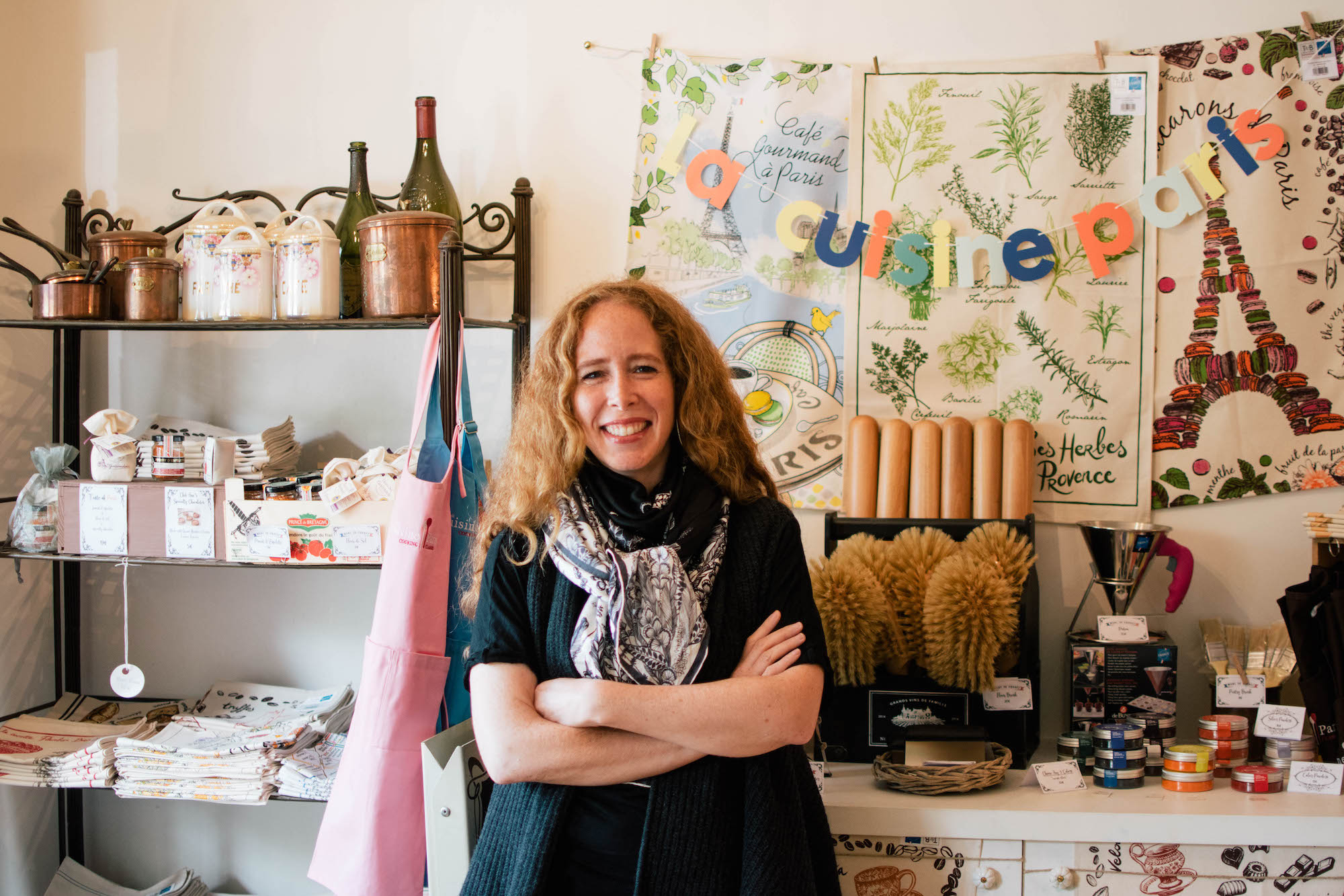 Jane Bertch, founder of La Cuisine Paris cooking school by the Seine River, smiles in the kitchen, which is flooded with light and filled with odds and ends: neatly folded tea towels; copper jars; and fun French food pictures depicting the Eiffel Tower, the herbs of Provence, and a bistro.