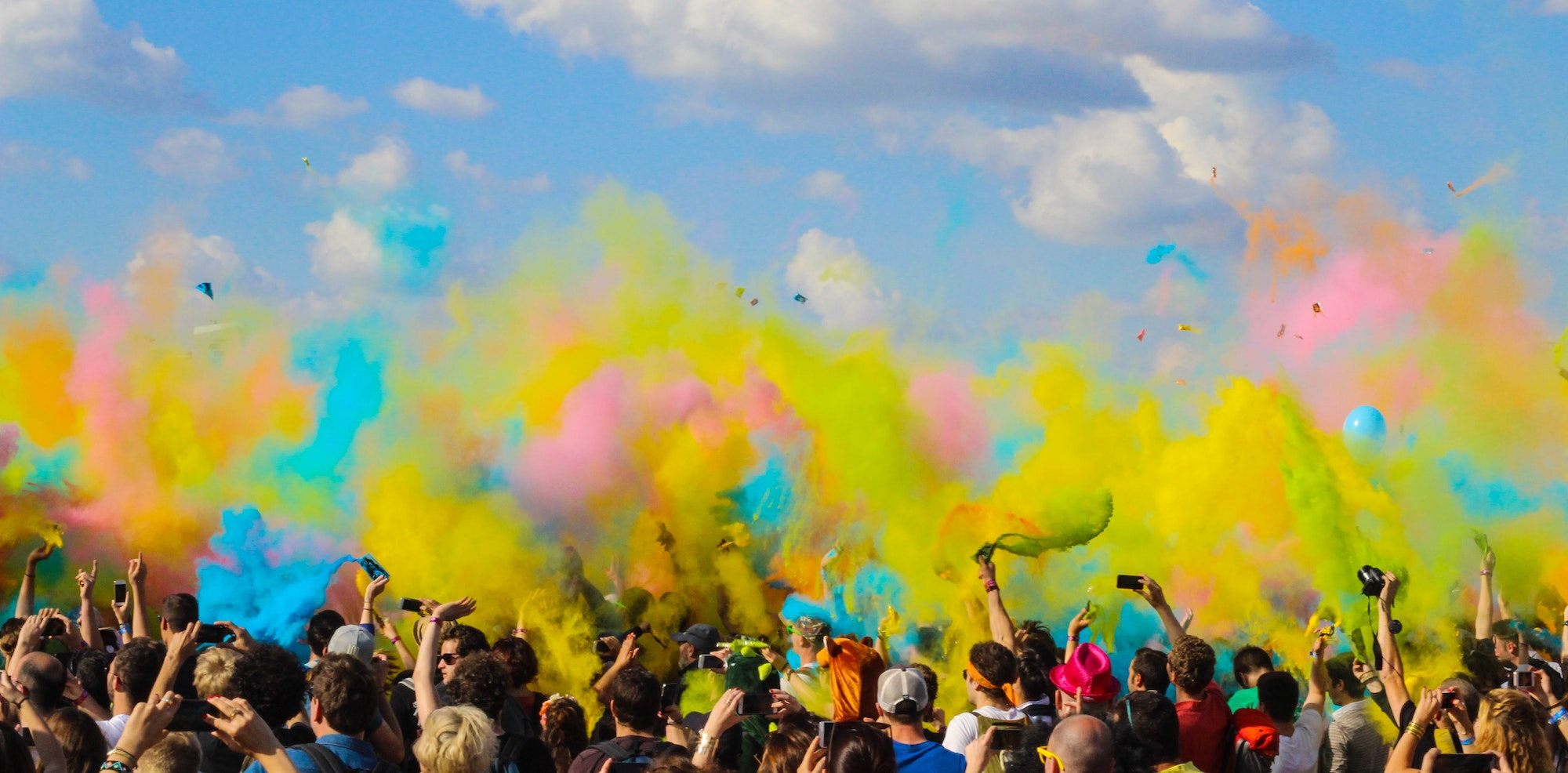 A crowd of people with a cloud of colorful paints above as they celebrate Holi festival in Paris in March.