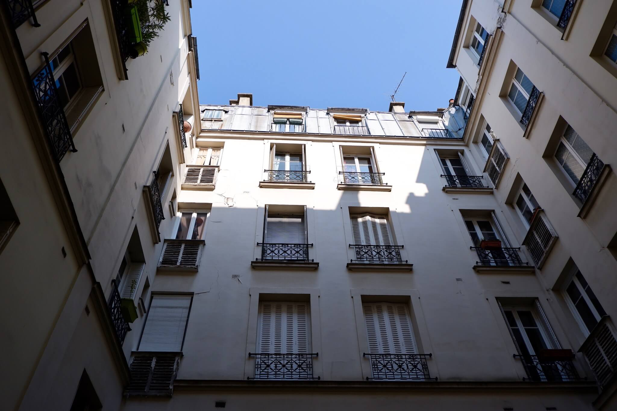 The courtyard view of Ali's Paris apartment, sunlight cast at the top of the building.