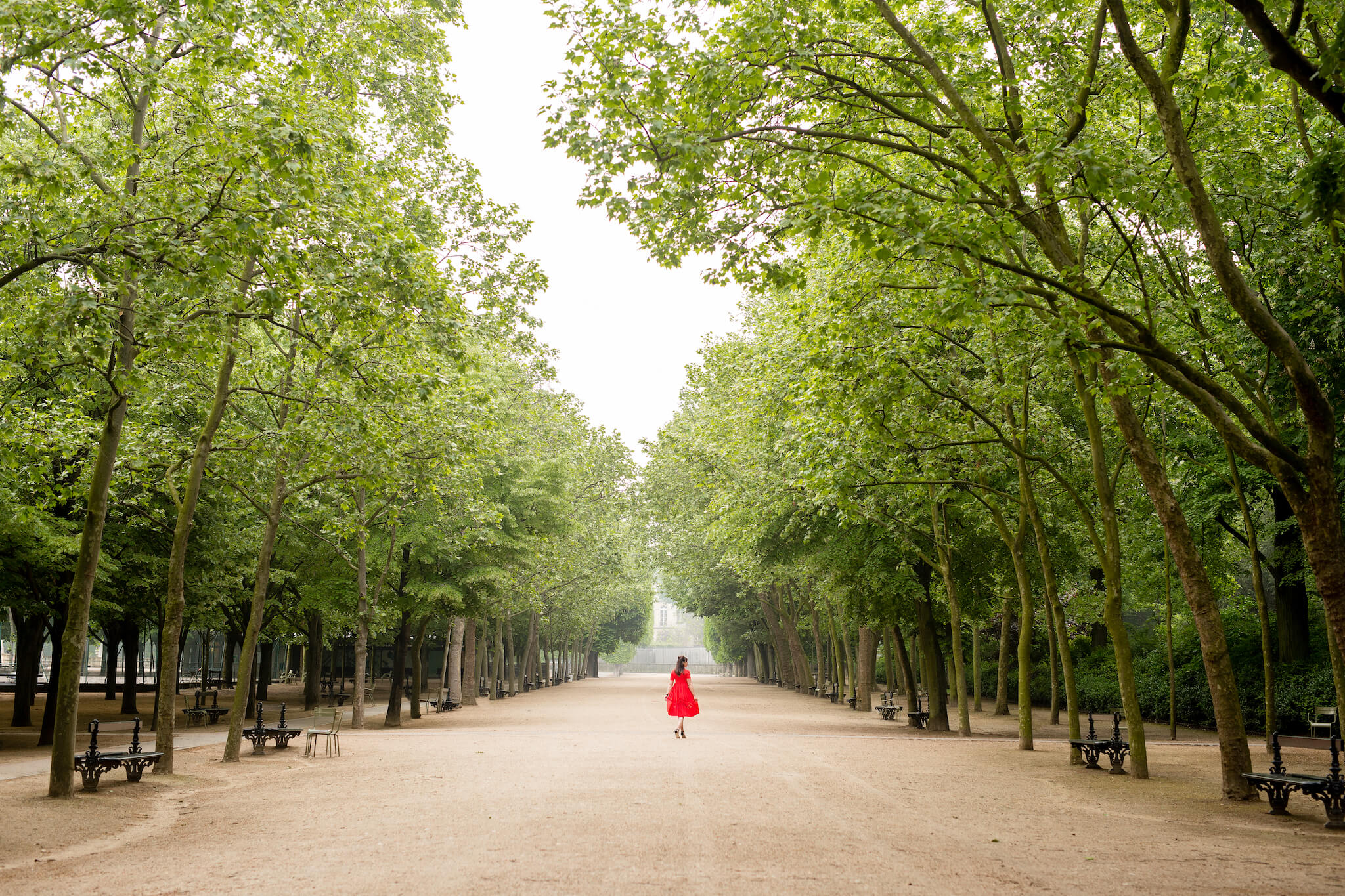 Rebecca Plotnick, travel photographer and blogger at Everyday Parisian, takes a twirl in an empty Tuileries garden, her bright red dress punctuating the verdant trees.