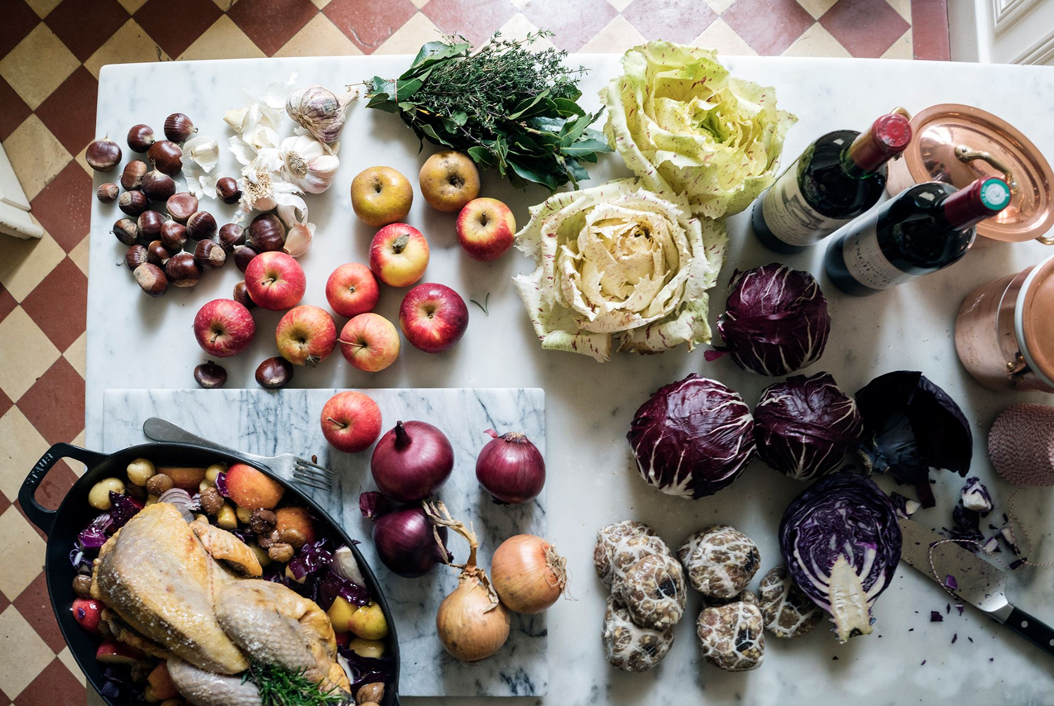 A sunlit-flooded table overflows with fresh produce: Leafy greens; chestnuts; a chicken to roast; apples; and, of course, wine.