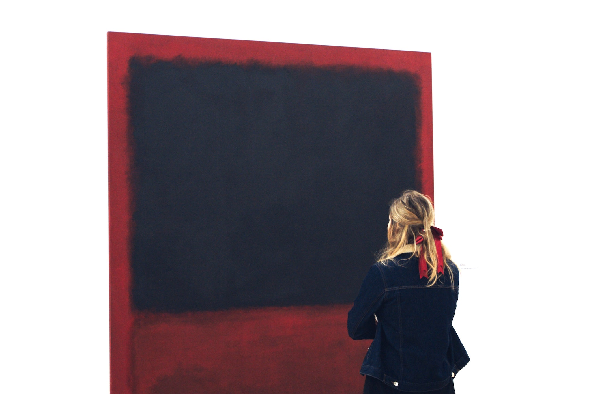A blonde woman standing infant of a Rothko painting. She's wearing a denim jacket and has a red ribbon in her hair. The Rothko painting is dark red with a black square.