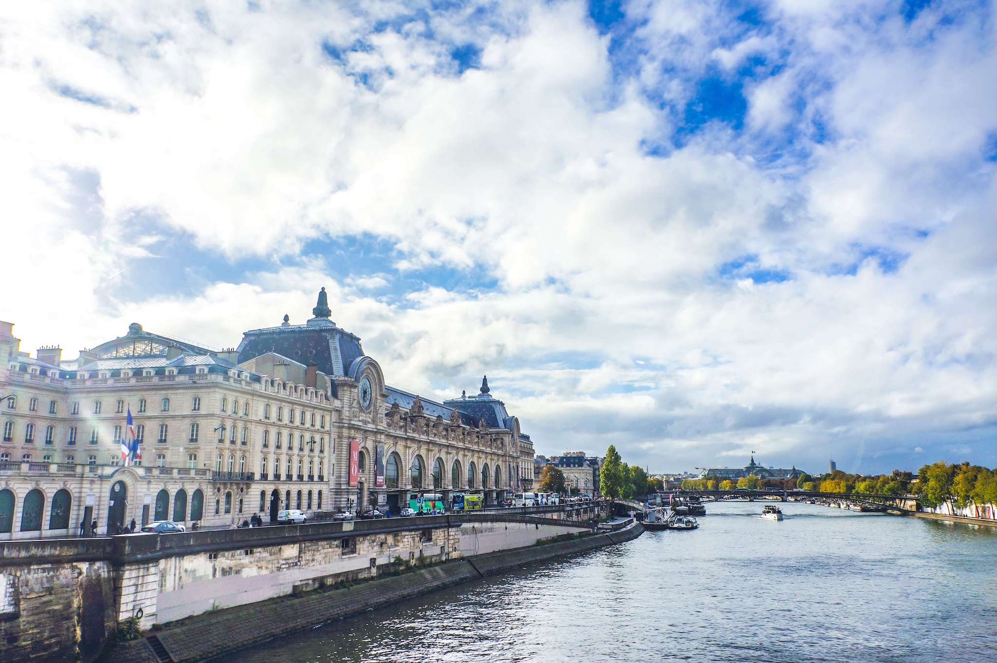 The outside of the D'Orsay Museum, on the Seine river in Paris. The sky is blue with some clouds, the sun is shining, the trees along the river are green. There is a boat going down the river.