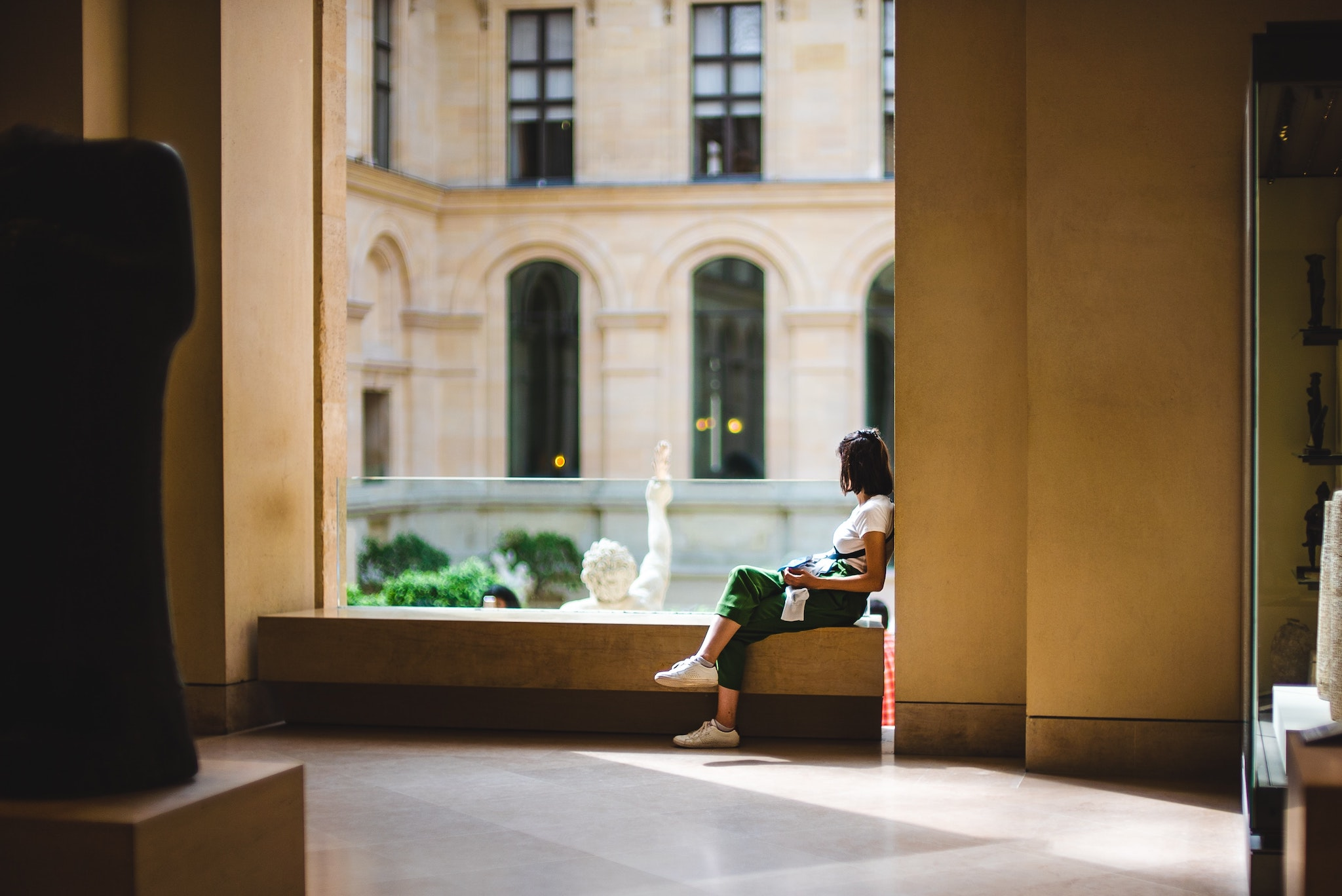 A brunette girl in a white t-shirt and green pants, wearing white sneakers, sitting on a bench seat in the Louvre Museum. She is looking away from the camera to an inner sculpture courtyard.