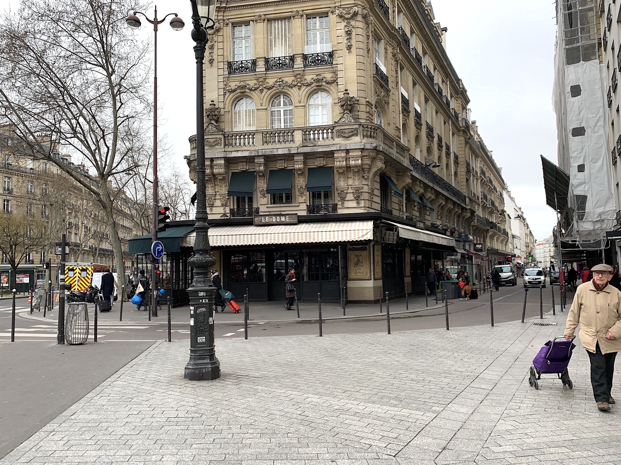 Paris under lockdown: A mostly empty street and closed café as solitary shoppers scamper to their destinations.