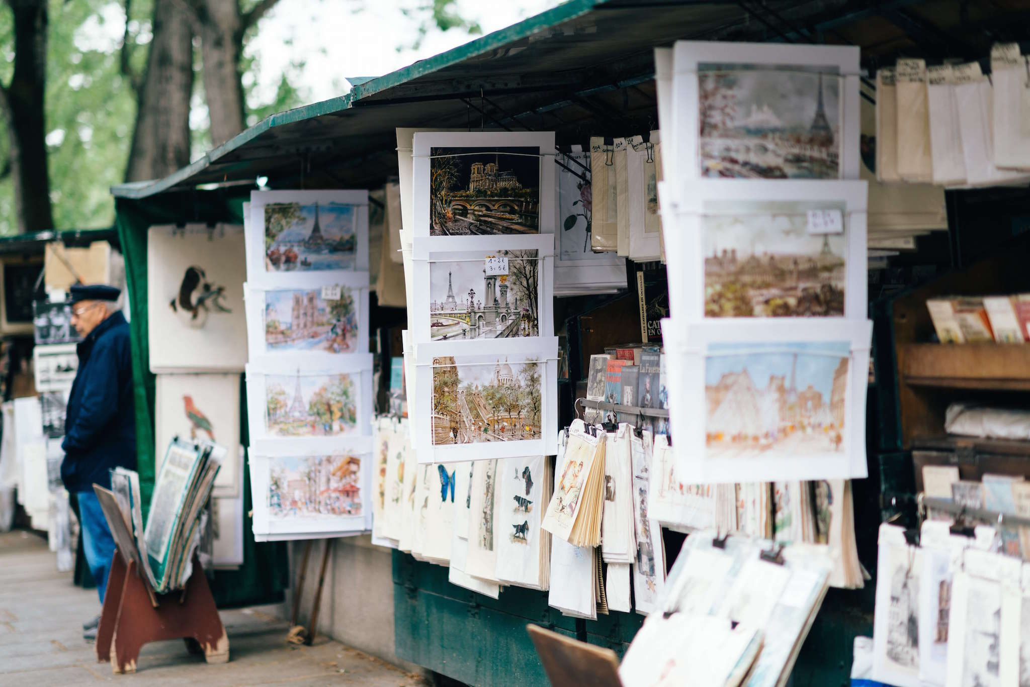An old man stands by stalls of art near the Seine in Pairs. Beautiful paintings that display scenes of Paris can be seen hanging from the stalls.