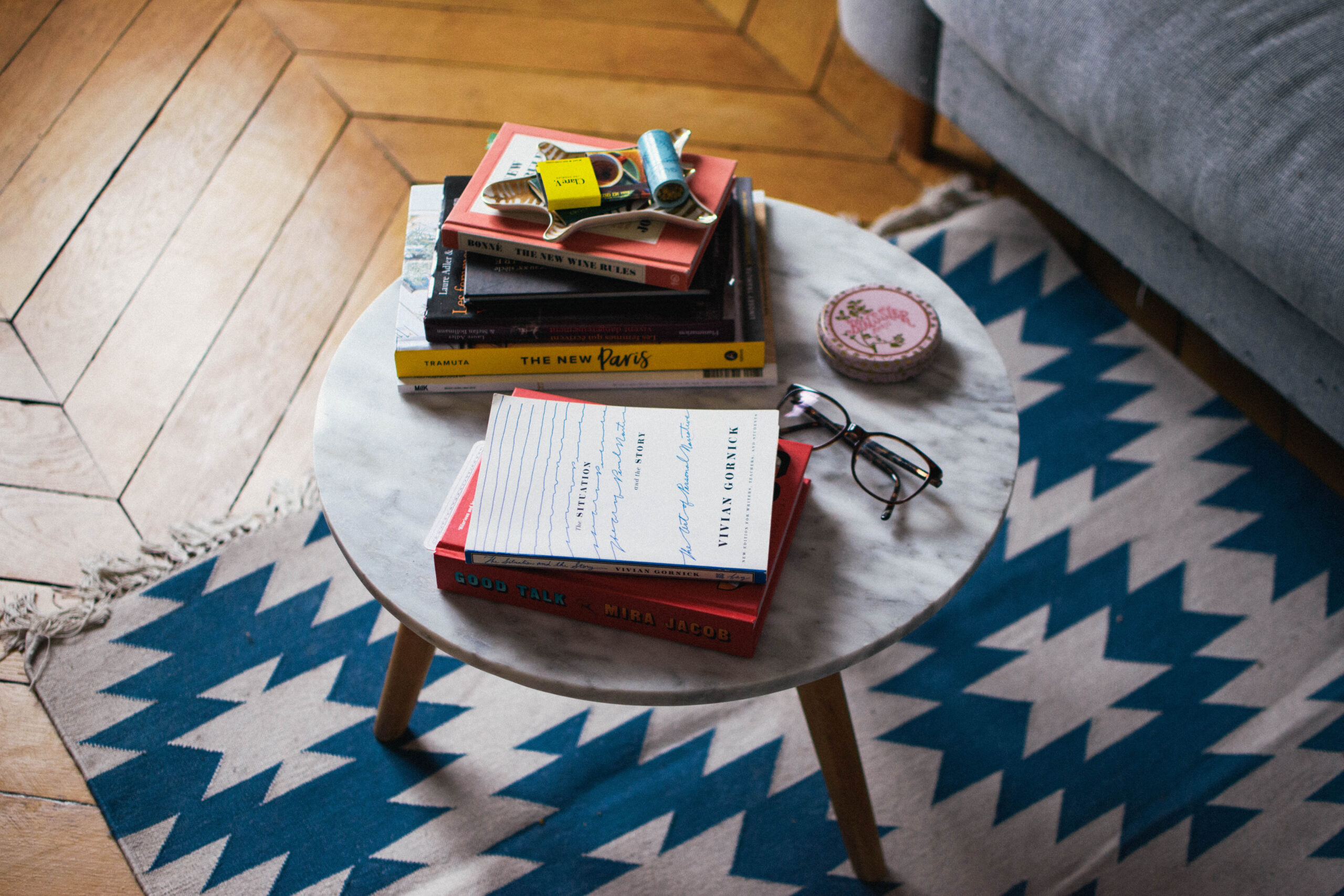 A marble table next to a gray couch in an apartment in Paris, atop are assorted items including books and a pair of glasses.