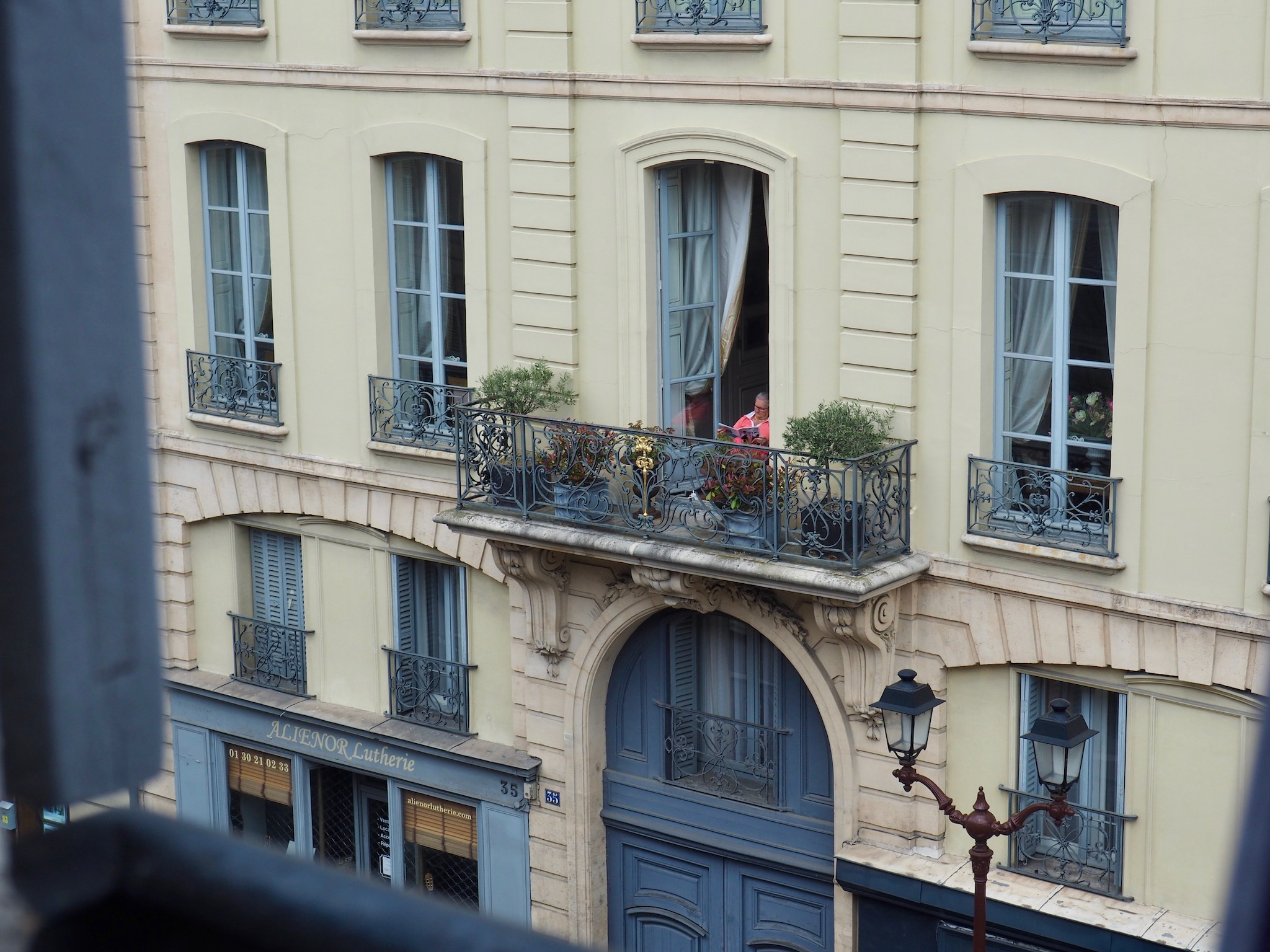 A woman in a pink shirts reads on her balcony in Paris, with her large door open and plants next to her on the balcony.