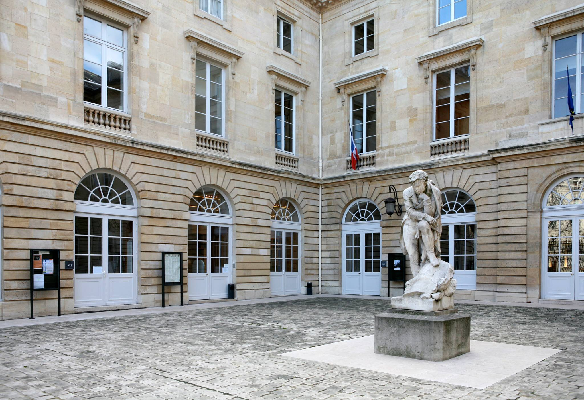 The Collège de France building in Paris. The building is stone and the window frames are white. There is a sculpture in the centre of the courtyard of a man with his foot resting on a head, his elbow resting on his knee, and his chin resting on his hand. There is a French flag hanging from one of the windows.