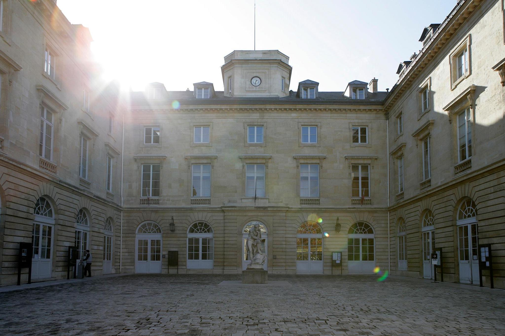 The Collège de France building in Paris. It is a stone symmetrical building with white window frames and an inner courtyard. At the top of the building in the centre is a clock. In the centre of the courtyard is a sculpture of a man. The sun is shining from behind the building in the top left hand corner, sending light streaks diagonally across the image.