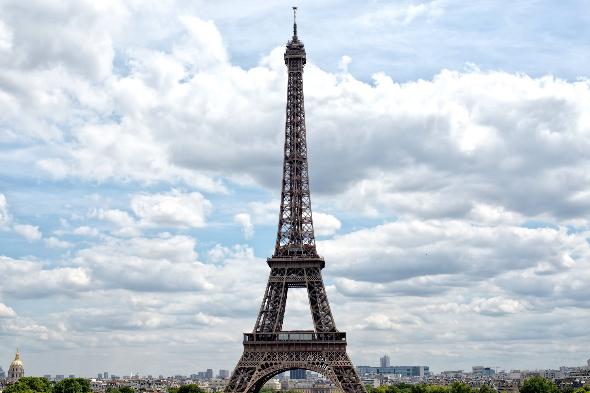 The Eiffel Tower stands tall on a bright, beautiful day in Paris