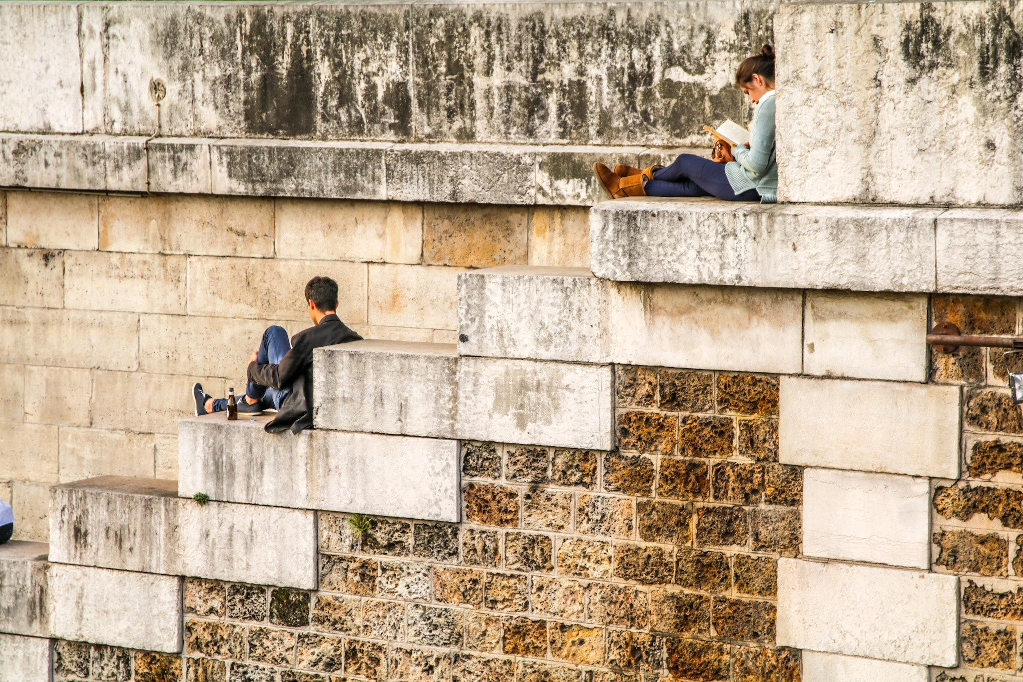 People are seen sitting on large stone steps near the Seine River in Paris; A man sits holding his leg and a woman a few steps above sits while reading a book.