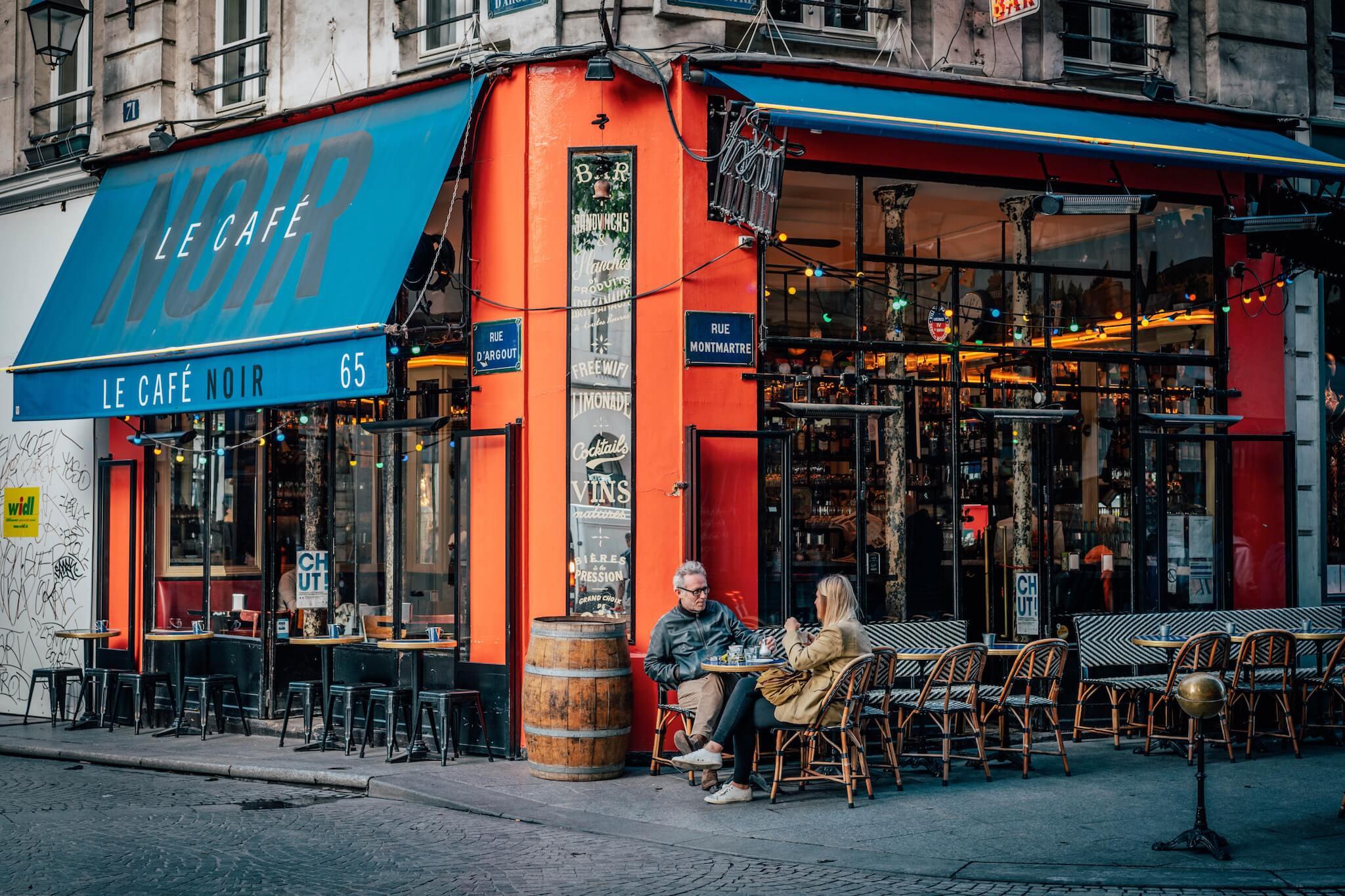 A man and a woman sit outside Le Café Noir in Paris.