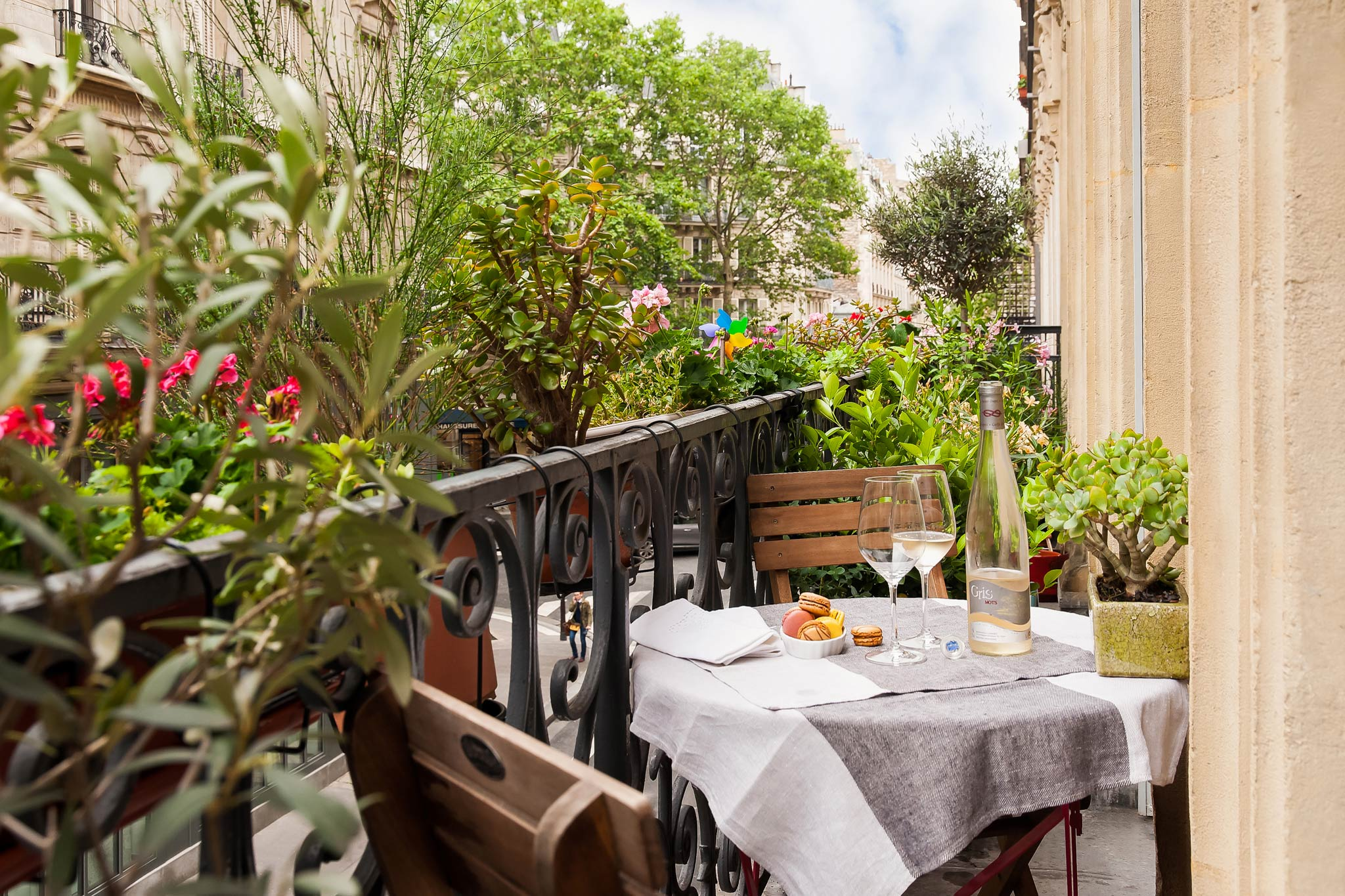 A table and chairs sits on the balcony of the Updated Parisian Charm apartment in Bastille. The table is set with macarons, wine glasses and a bottle of wine. The table has a tablecloth atop it and flowers and plants line the railing of the balcony.