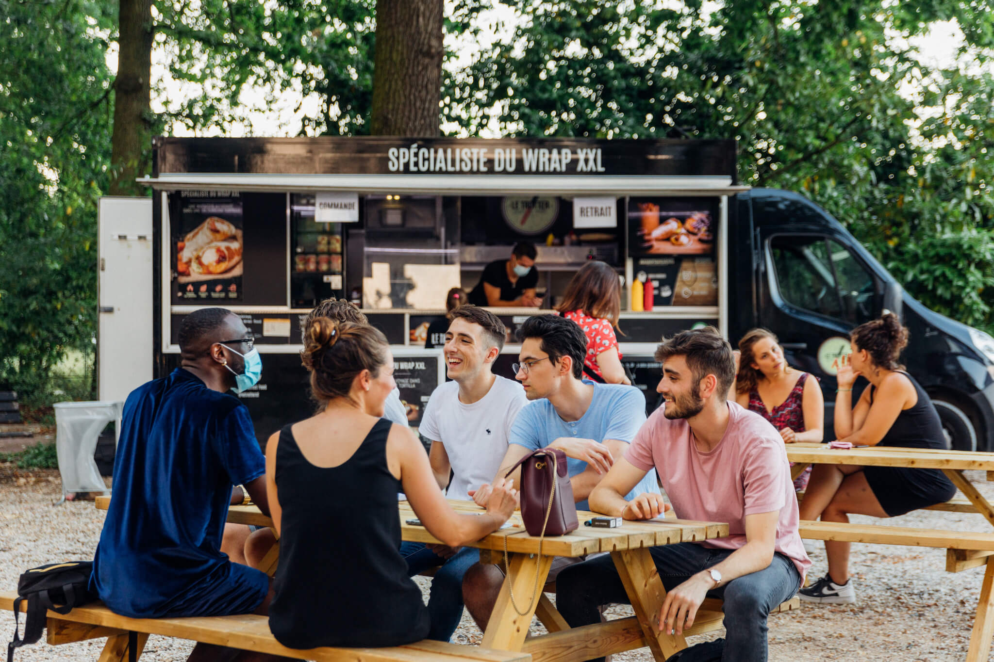 Two groups of people seated at two wooden bench tables in front of a black food truck which has the words 'specialiste du wrap xxl' on it. There is a server in the truck wearing a mask, on his phone. Behind the truck are green trees.