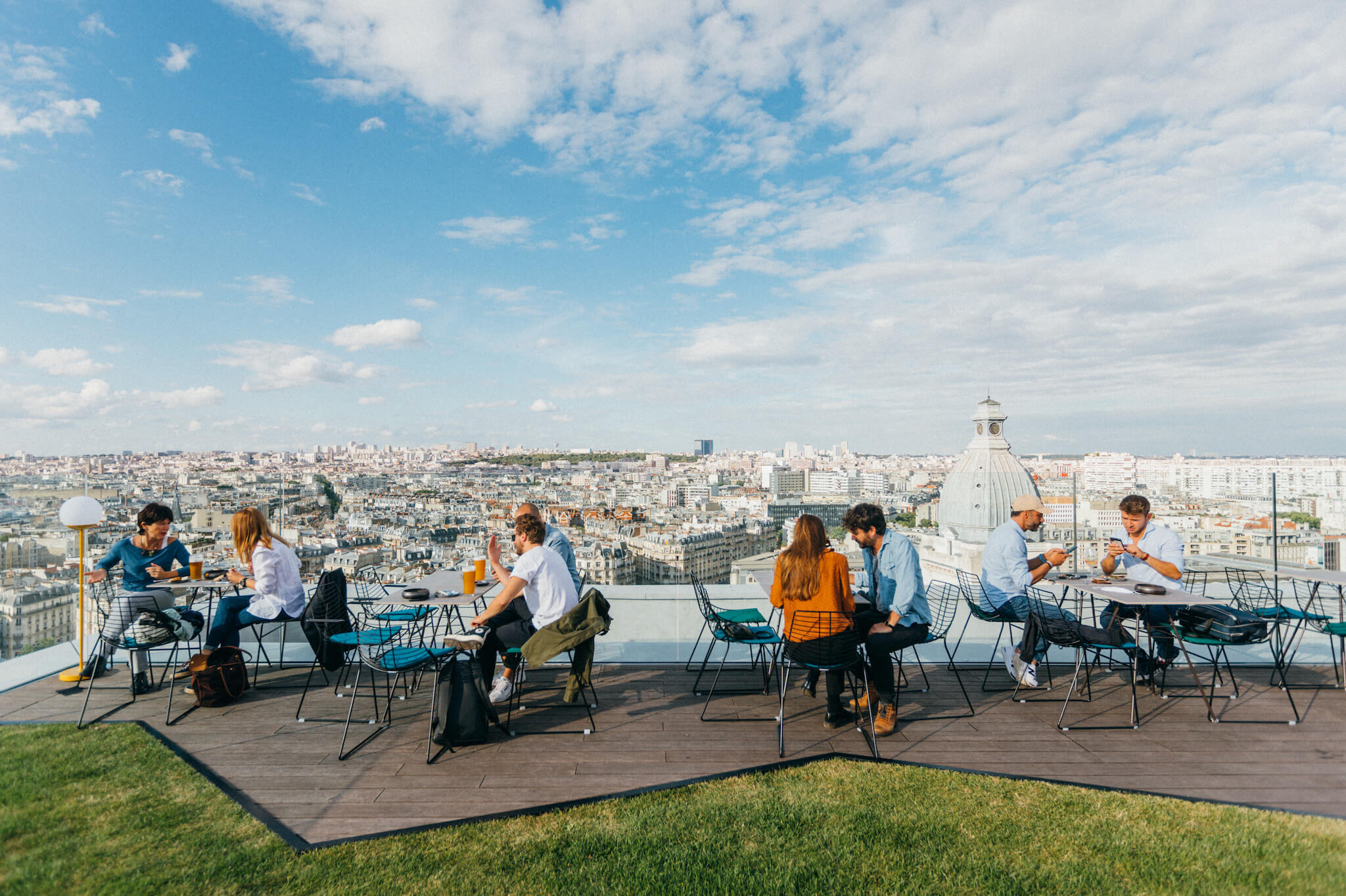 The terrace of Laho, a rooftop bar in Paris. There are four couples sitting at tables on a wooden patio with grass in front of them. Behind them is a view of the Parisian rooftops. It's a sunny day with a blue sky and some clouds.