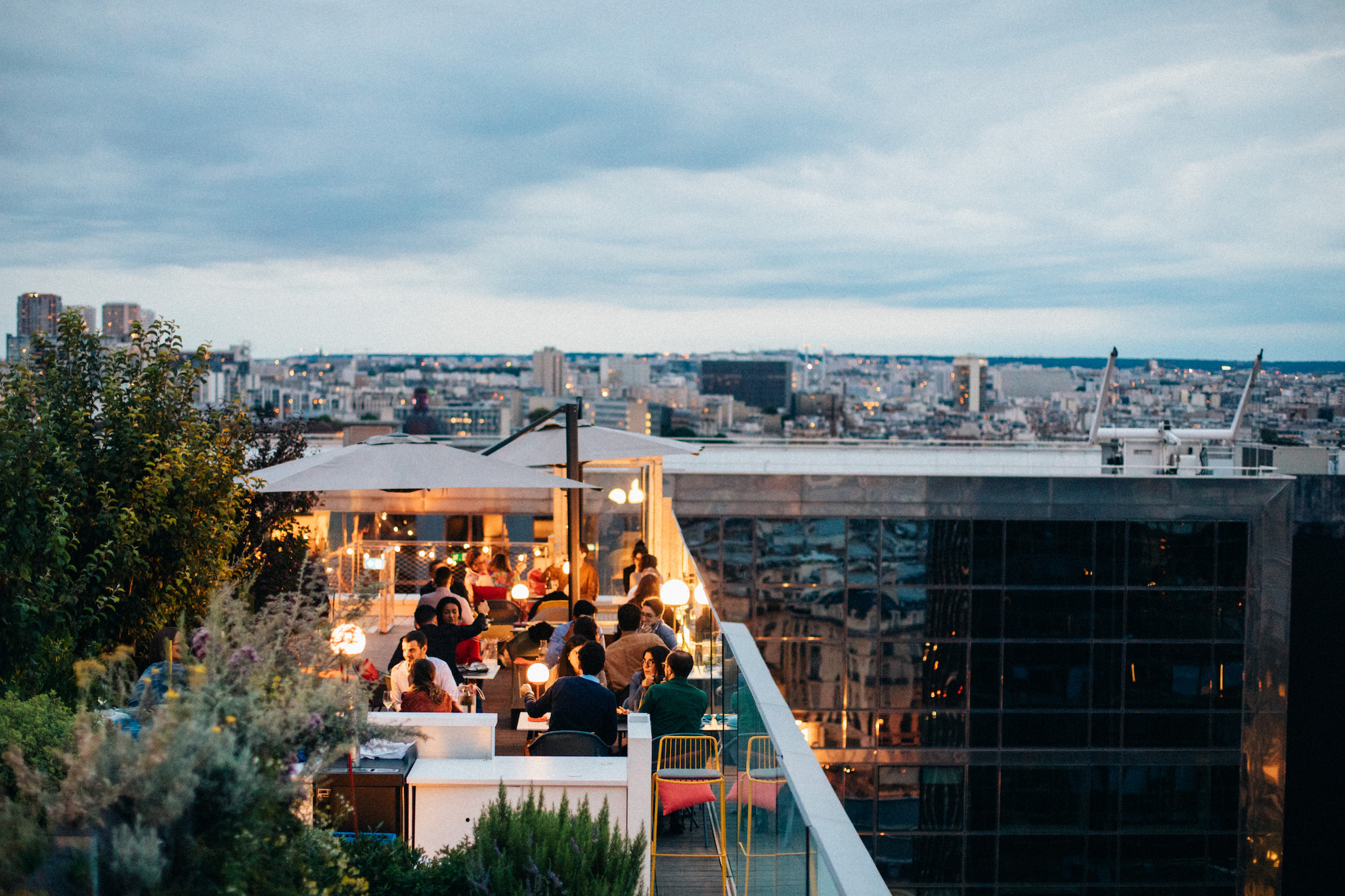 The terrace of the rooftop bar Laho. It is dusk and there are people seated at tables. The lights are on and they are seated underneath umbrellas. There are some trees and plants on the left. In the background you can see a view of Paris under a grey, cloudy sky.