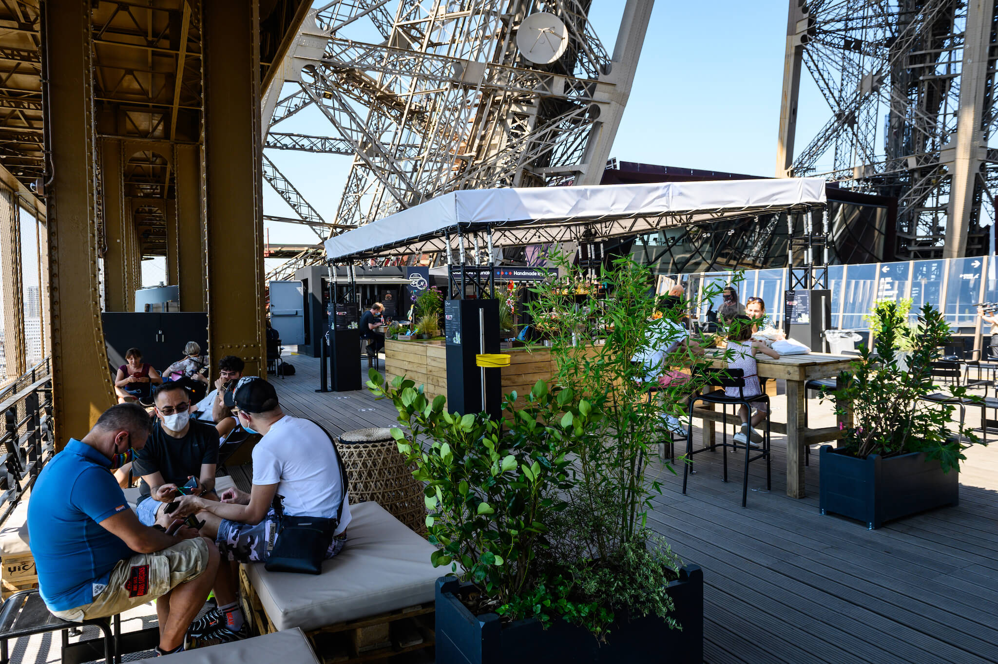 The wooden terrace of the Eiffel Tower in Paris. There are groups of people seated, some wearing face masks. You can see the pillars of the Eiffel Tower around them. There is a wooden bar in the middle with a white tarp roof. There are also some pot plants.
