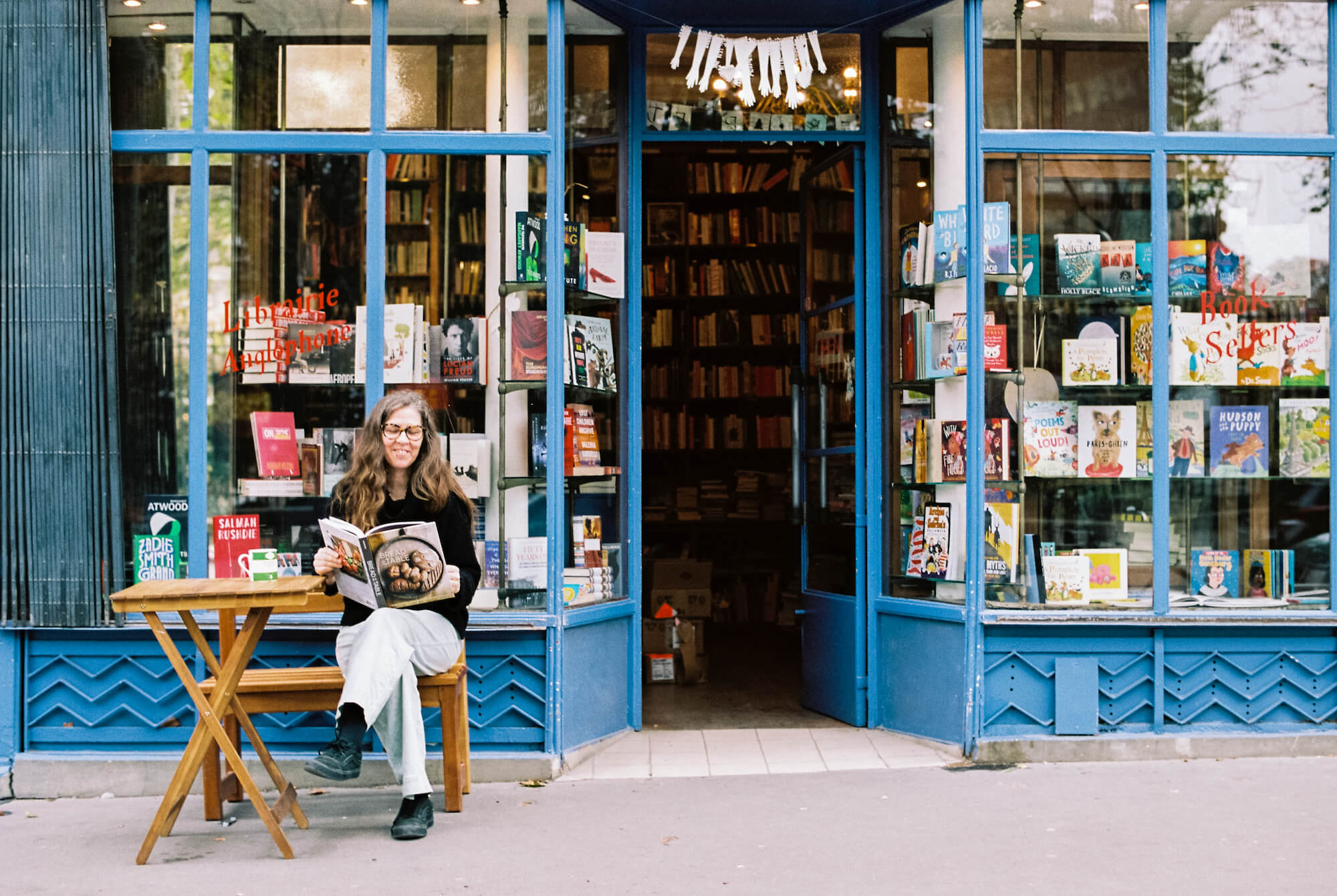 Penelope Fletcher, bookseller at the Red Wheelbarrow, sits outside the bright, blue and beloved bookstore with a magazine in her hands and smile on her face.