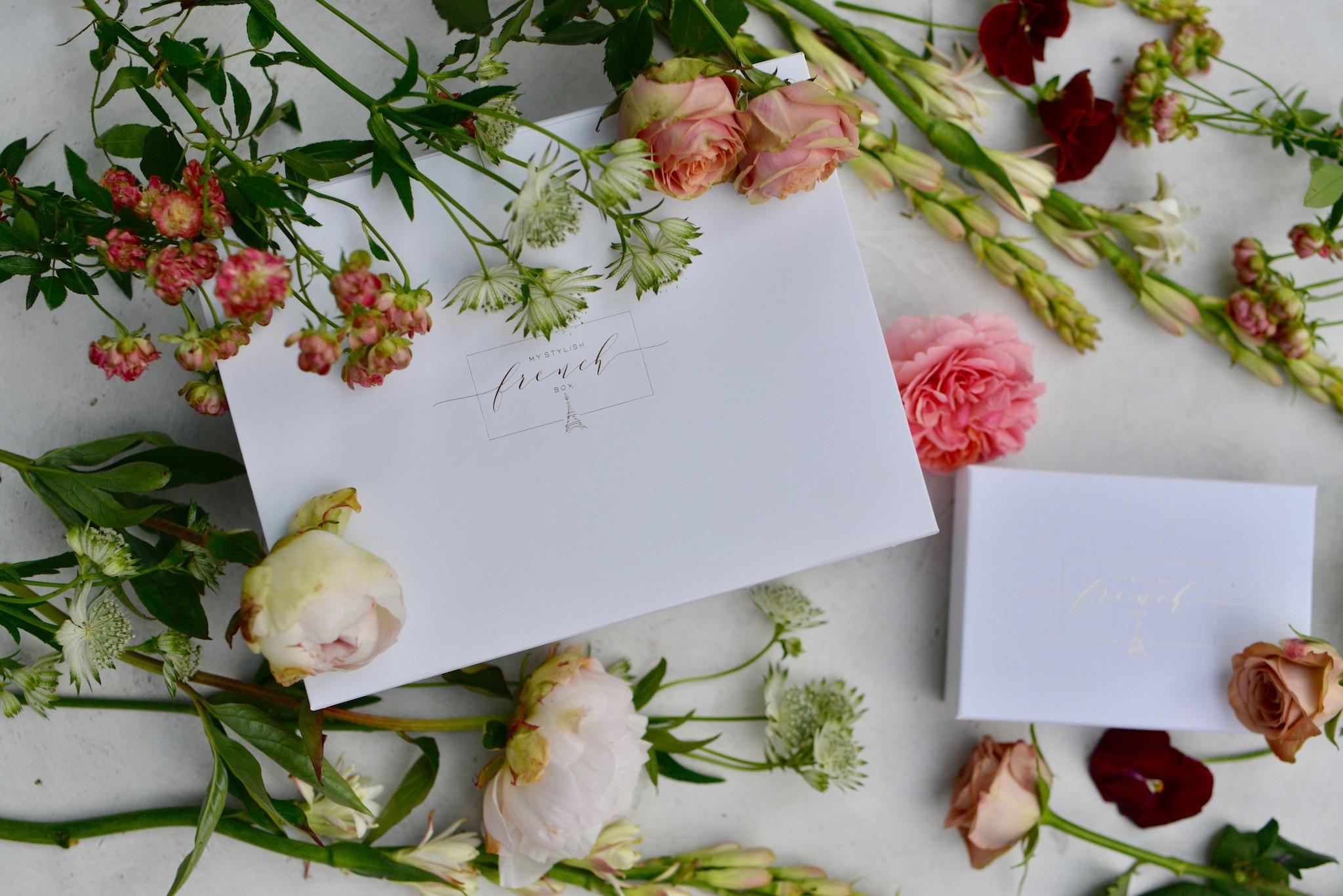 A handwritten invitation lying amidst flowers.
