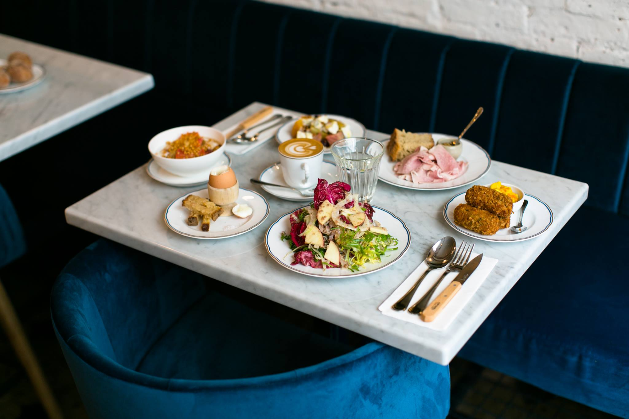 Food, including a boiled egg, cup of coffee, ham and a salad sits on a table at Holybelly 19.
