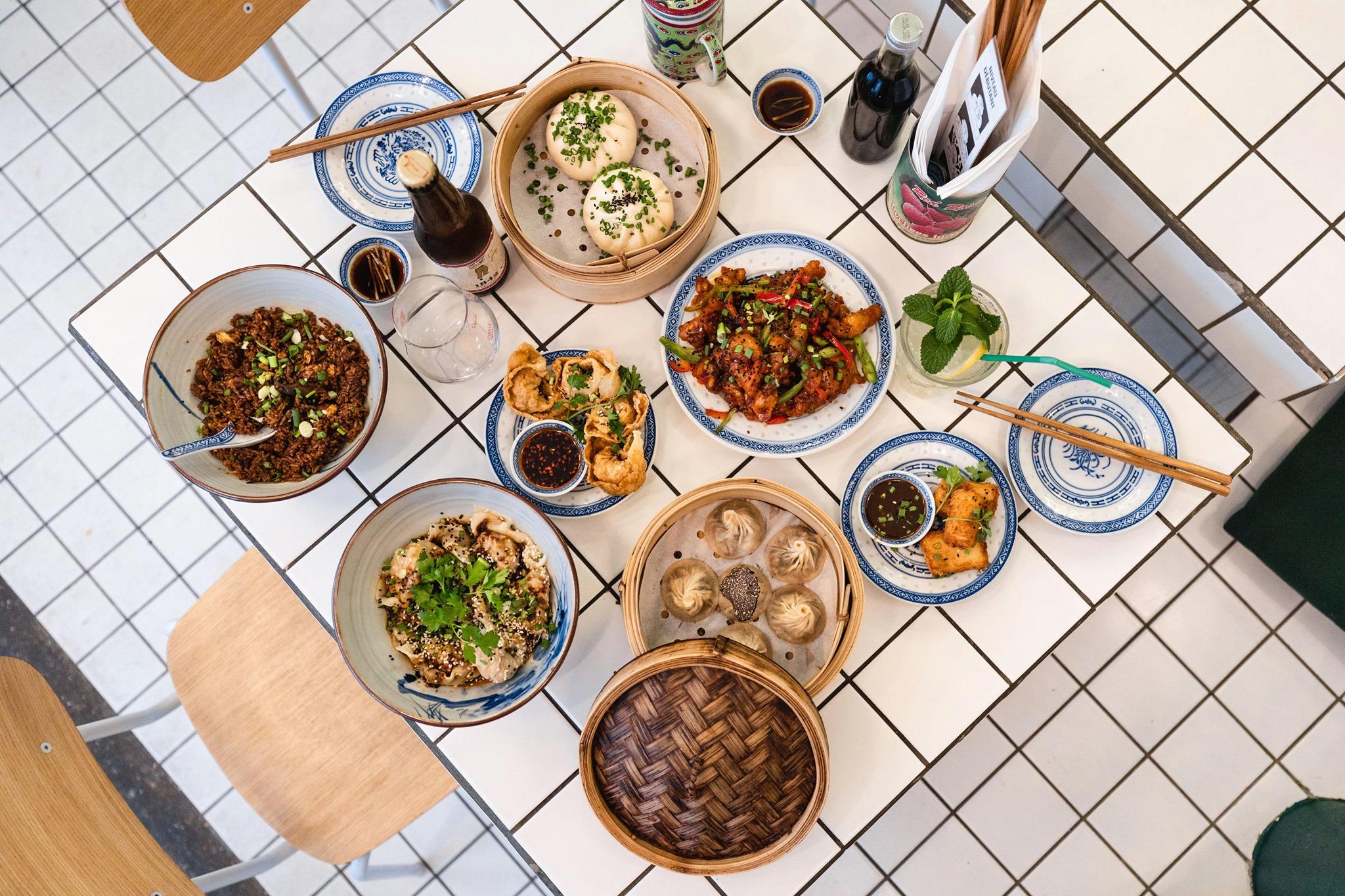 An overhead shot of food at Petit Bao, including bao buns, chao mian, wontons and more.