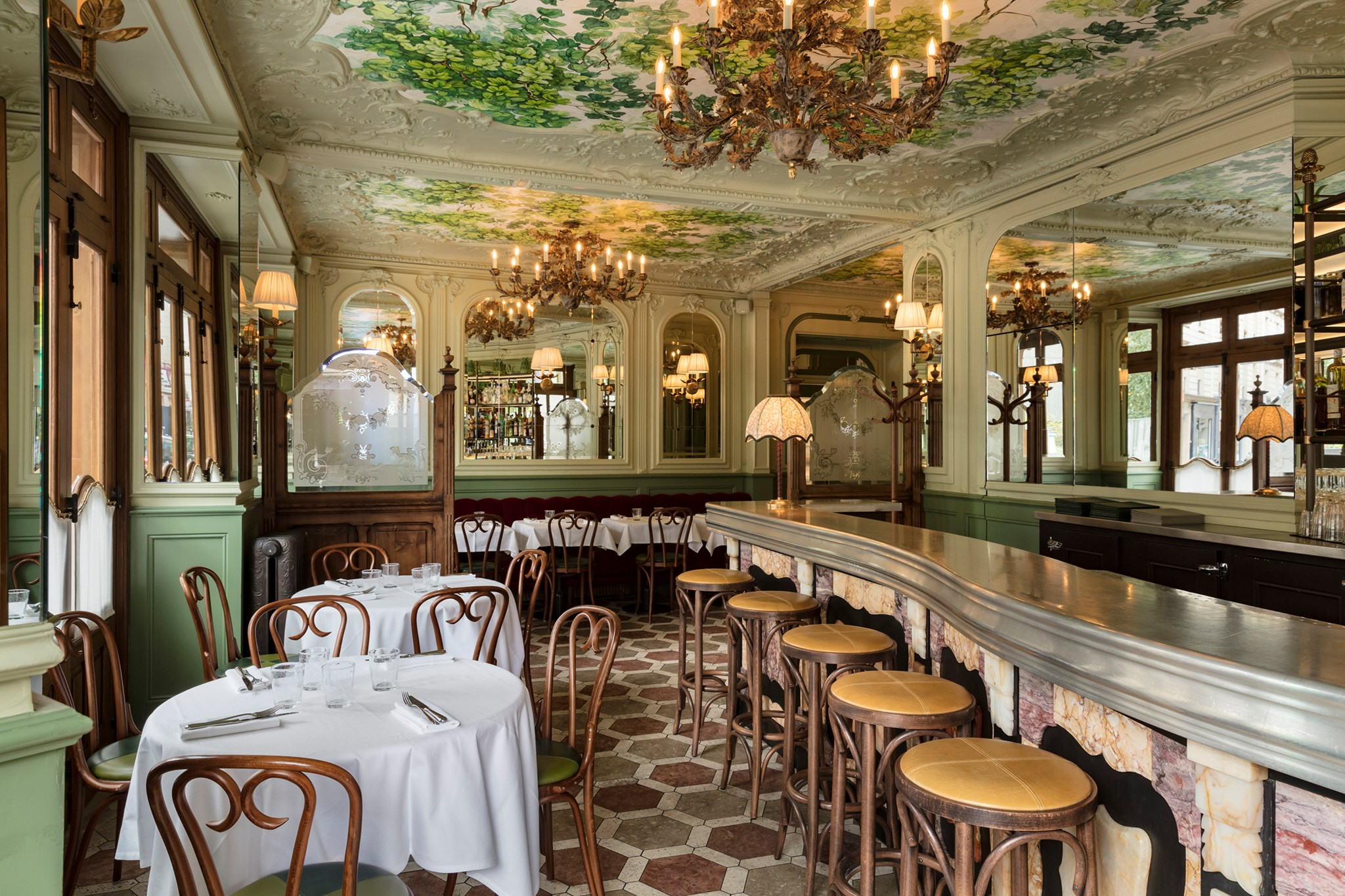 The interior of Le Chardenoux restaurant, decorated with beautiful gold chandeliers and green detailing on the walls and ceiling.